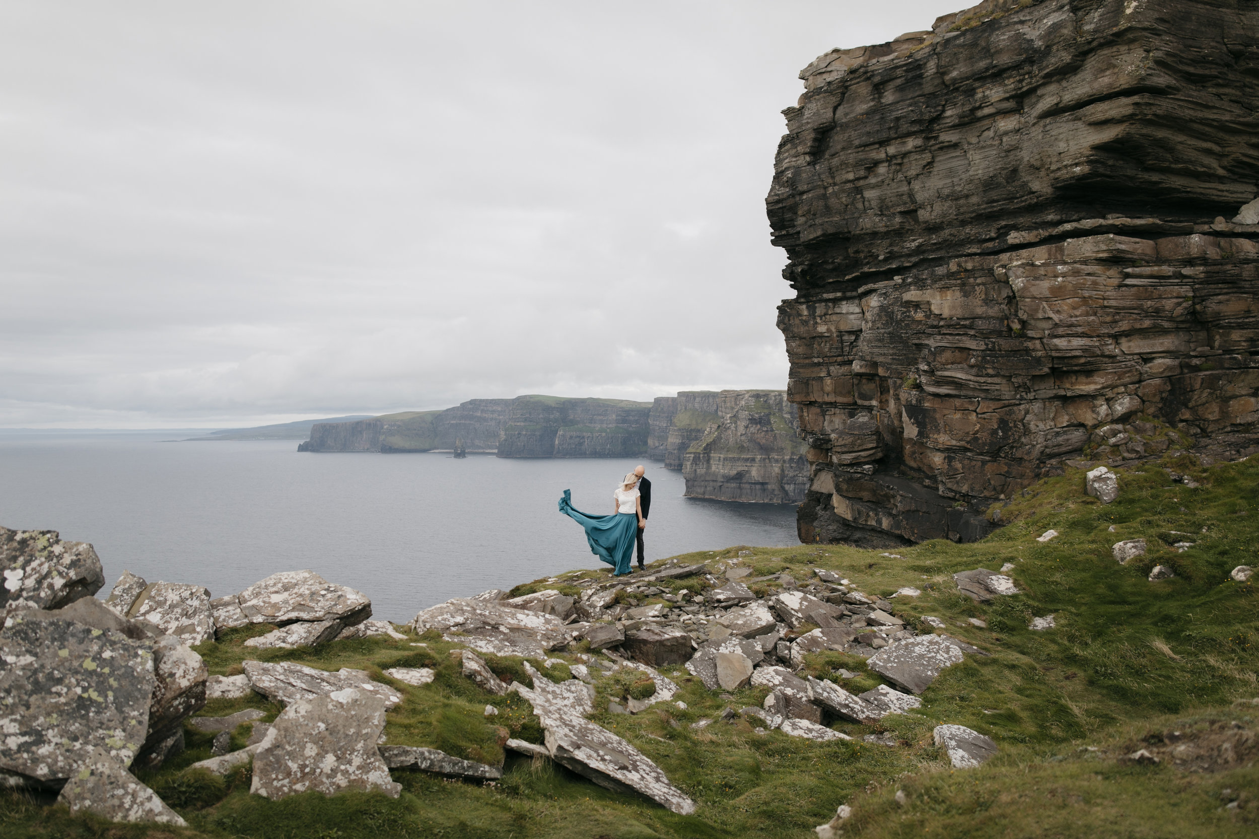 A lovely couple embrace each other during epic photography session at Cliffs of Moher by Ireland Elopement Photographers Colby and Jess