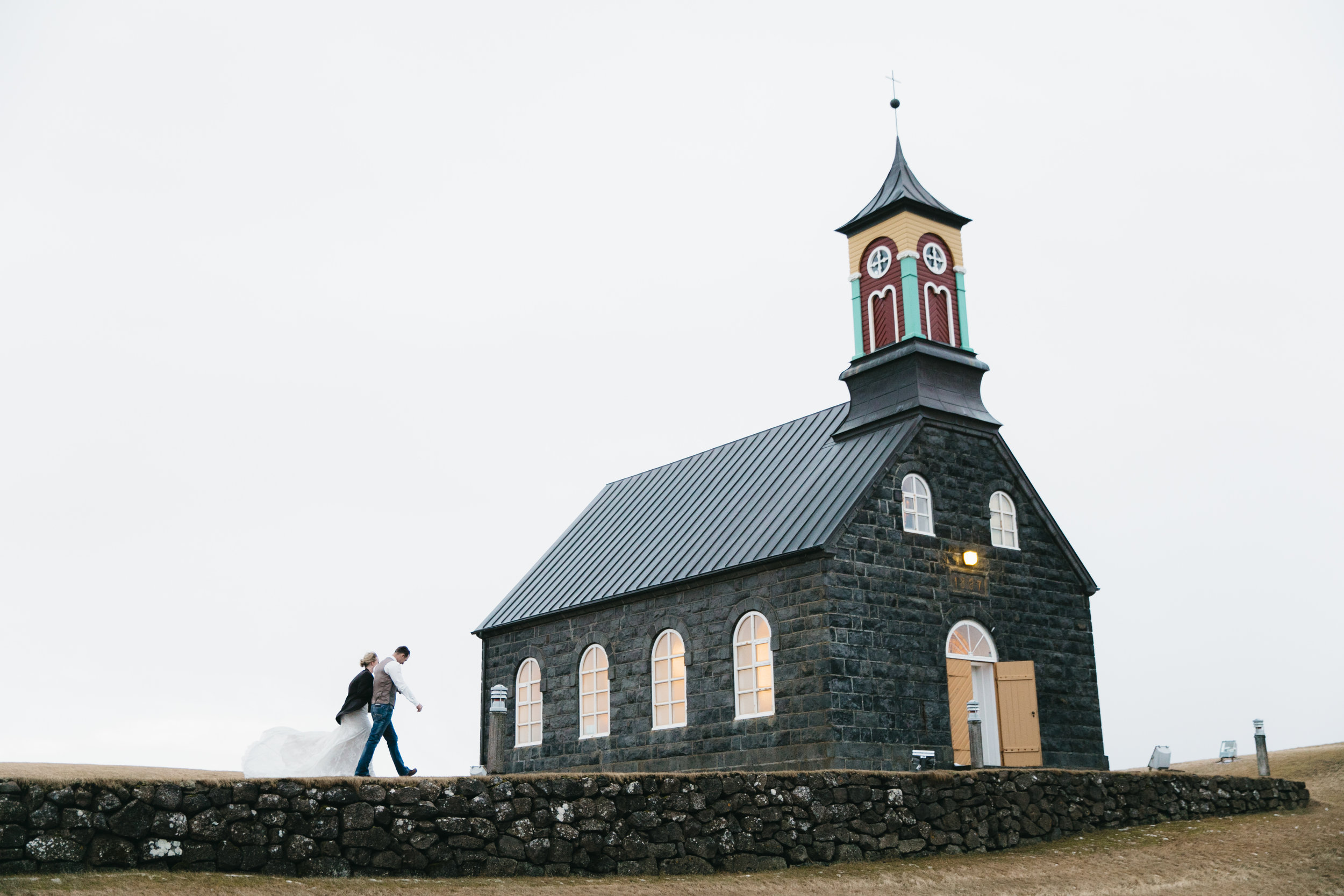 Couple walks to Church at Hvalsnes for elopement ceremony, photo by Iceland Wedding Photographers Colby and Jess.