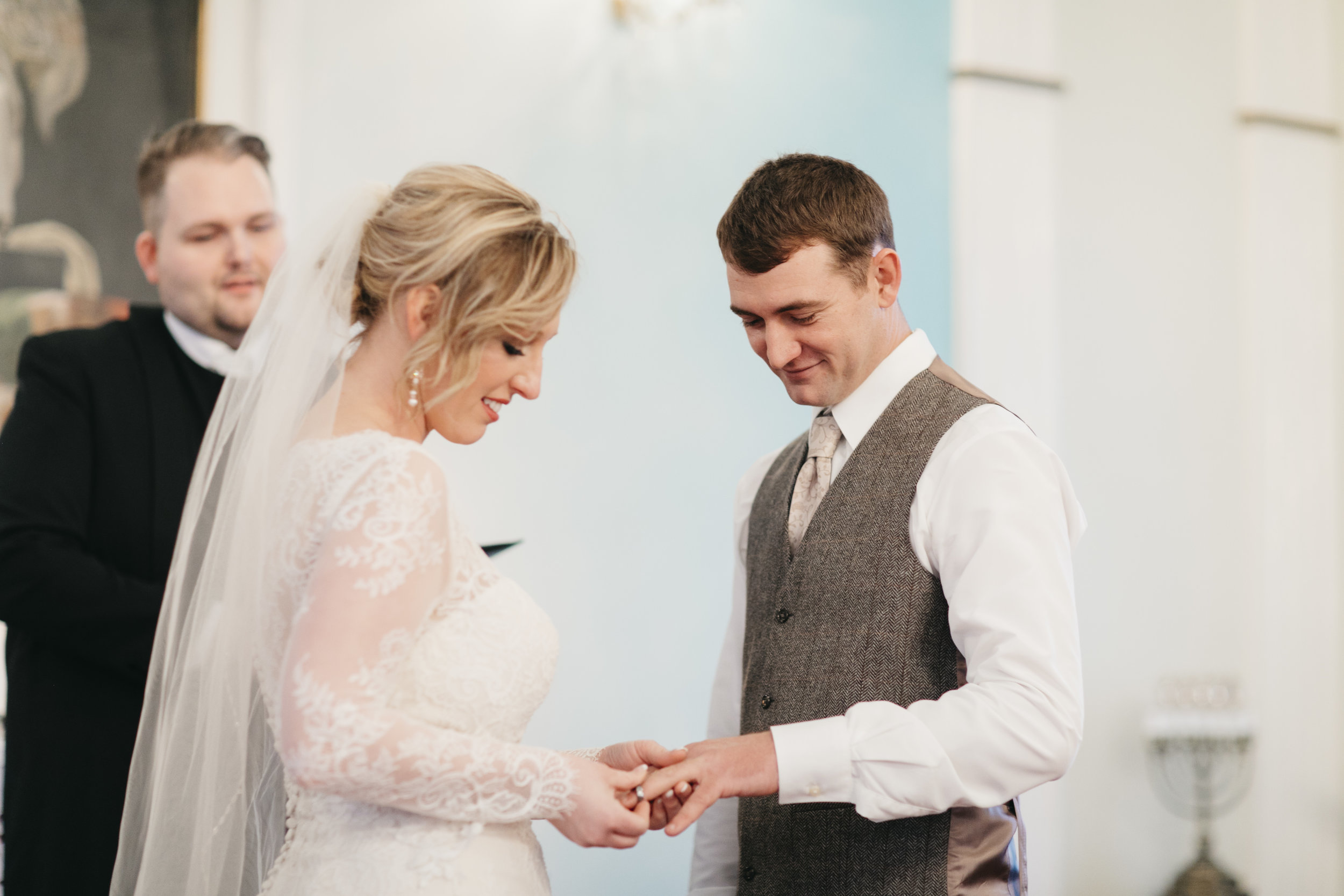 A beautiful bride puts the wedding ring on her groom's finger in Hvalsneskirkja church during their Iceland Elopement.
