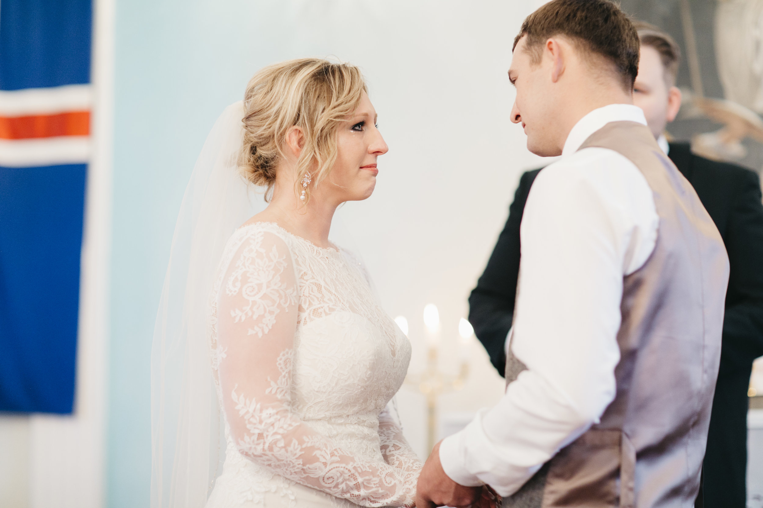 An emotional bride listens to her groom's vows during their elopement ceremony in Hvalsneskirkja Church in Iceland while photographed by Colby and Jess.