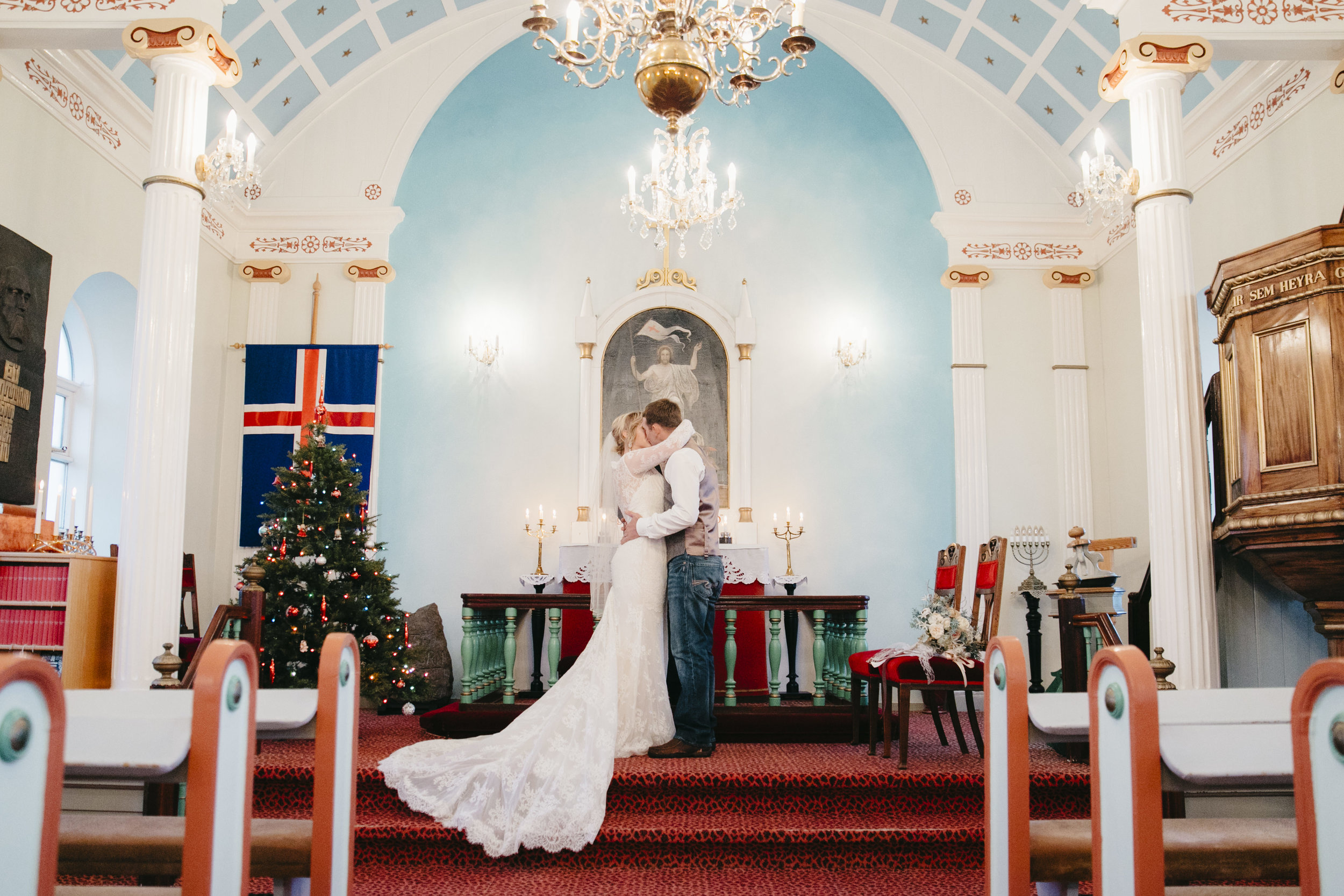 The bride and groom seal their vows with a kiss in Hvalsneskirkja Church while eloping in Iceland with their photographers Colby and Jess.