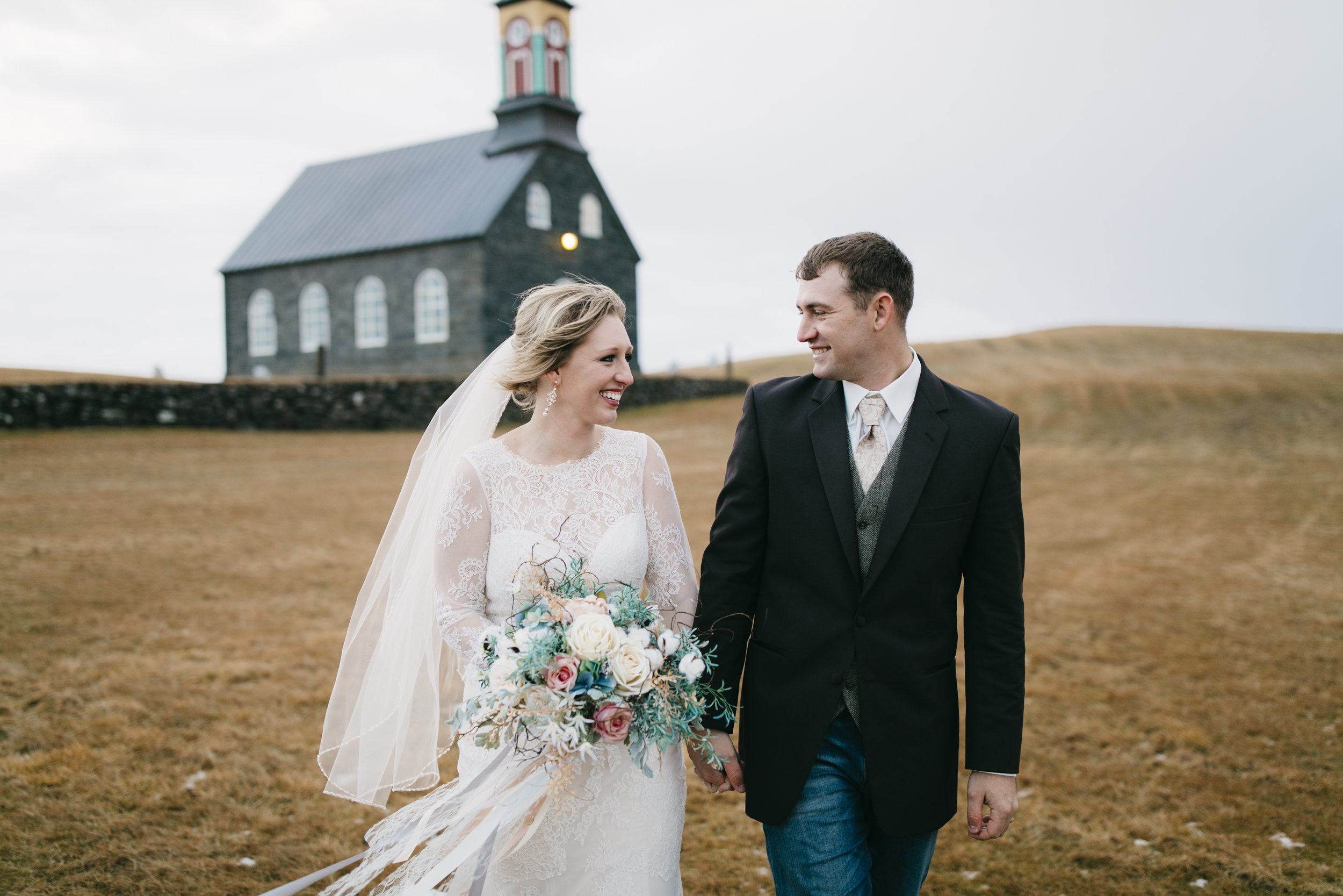A couple giddy with excitement after their wedding in Hvalsneskirkja church with their Iceland Elopement photographers Colby and Jess, colbyandjess.com