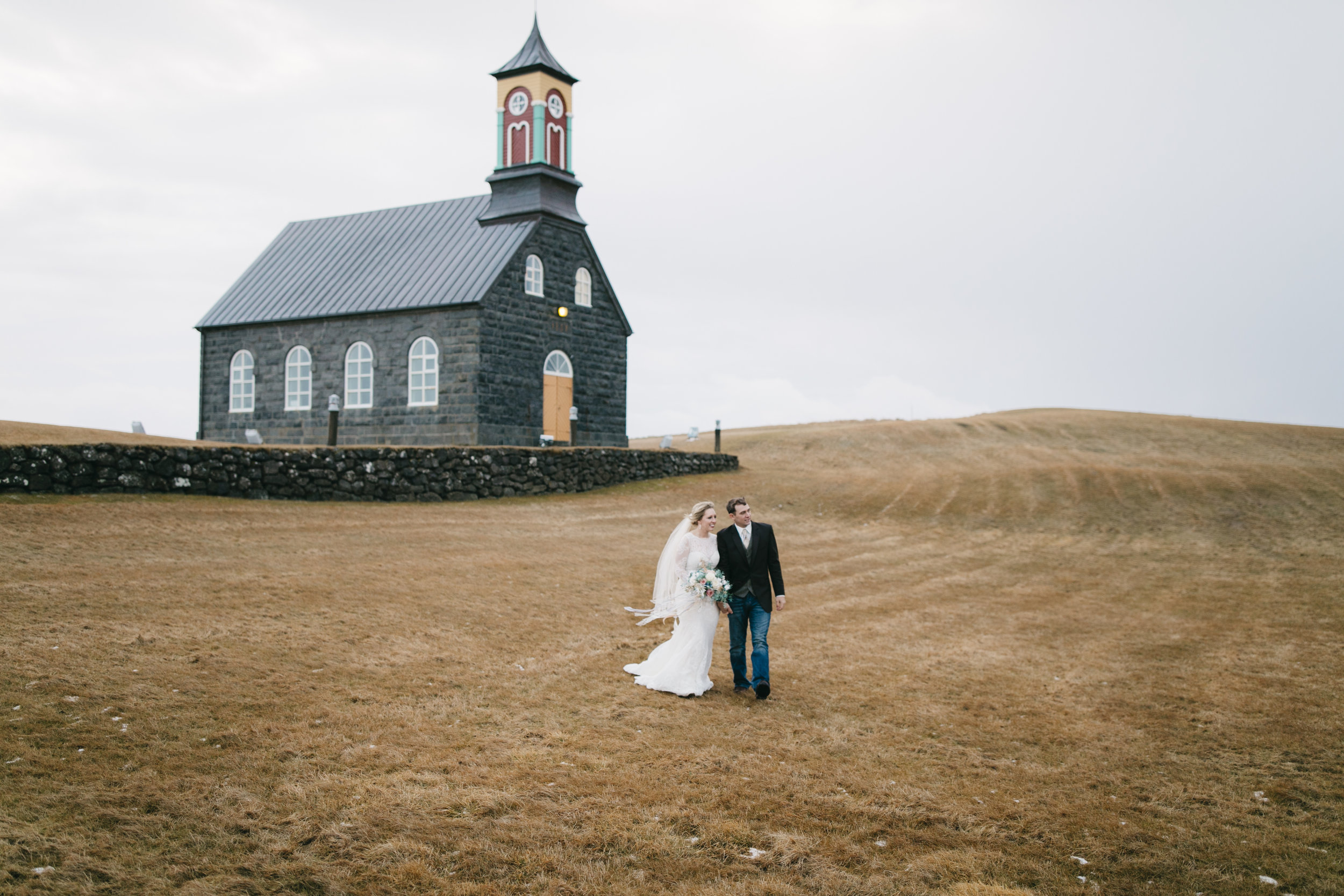 A couple who just eloped in Iceland stand in front of Hvalsneskirkja Church with their Iceland Elopement photographers Colby and Jess, colbyandjess.com