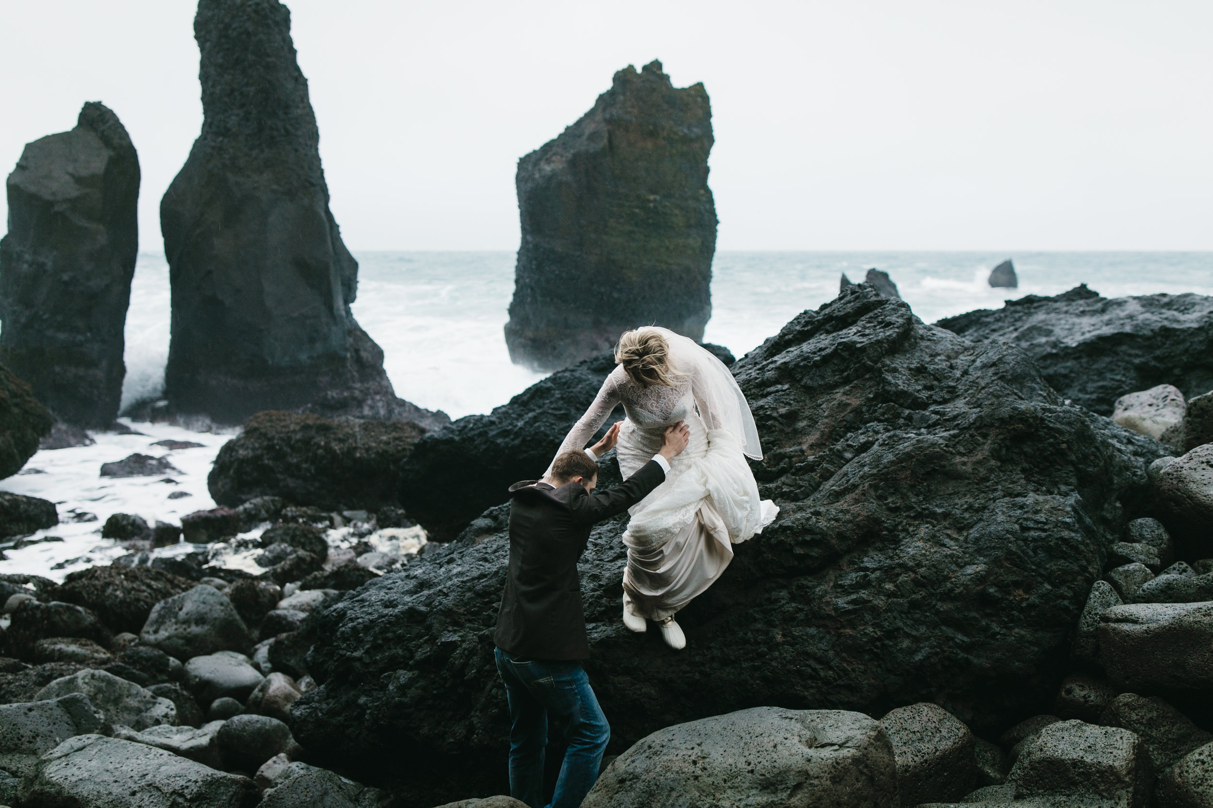A groom helps his adventurous bride down from rocks on Reykjanes peninsula while Iceland Elopement photographers Colby and Jess capture their adventure.
