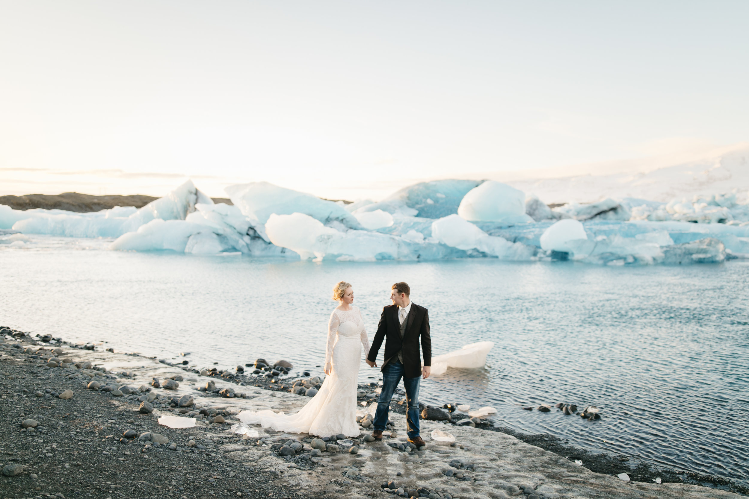 A happy couple walks along beach beside glaciers during Iceland Elopement Photography session by Colby and Jess.