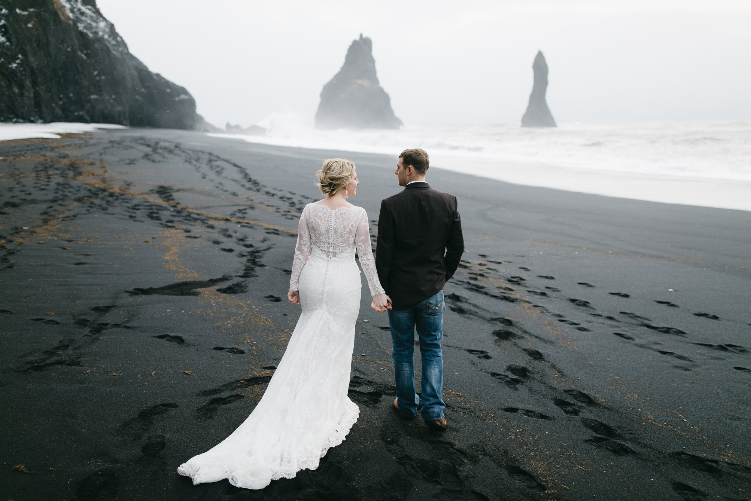 A couple takes a romantic walk on the black sand beach in Vik after their Iceland Elopement with wedding photographers Colby and Jess, colbyandjess.com