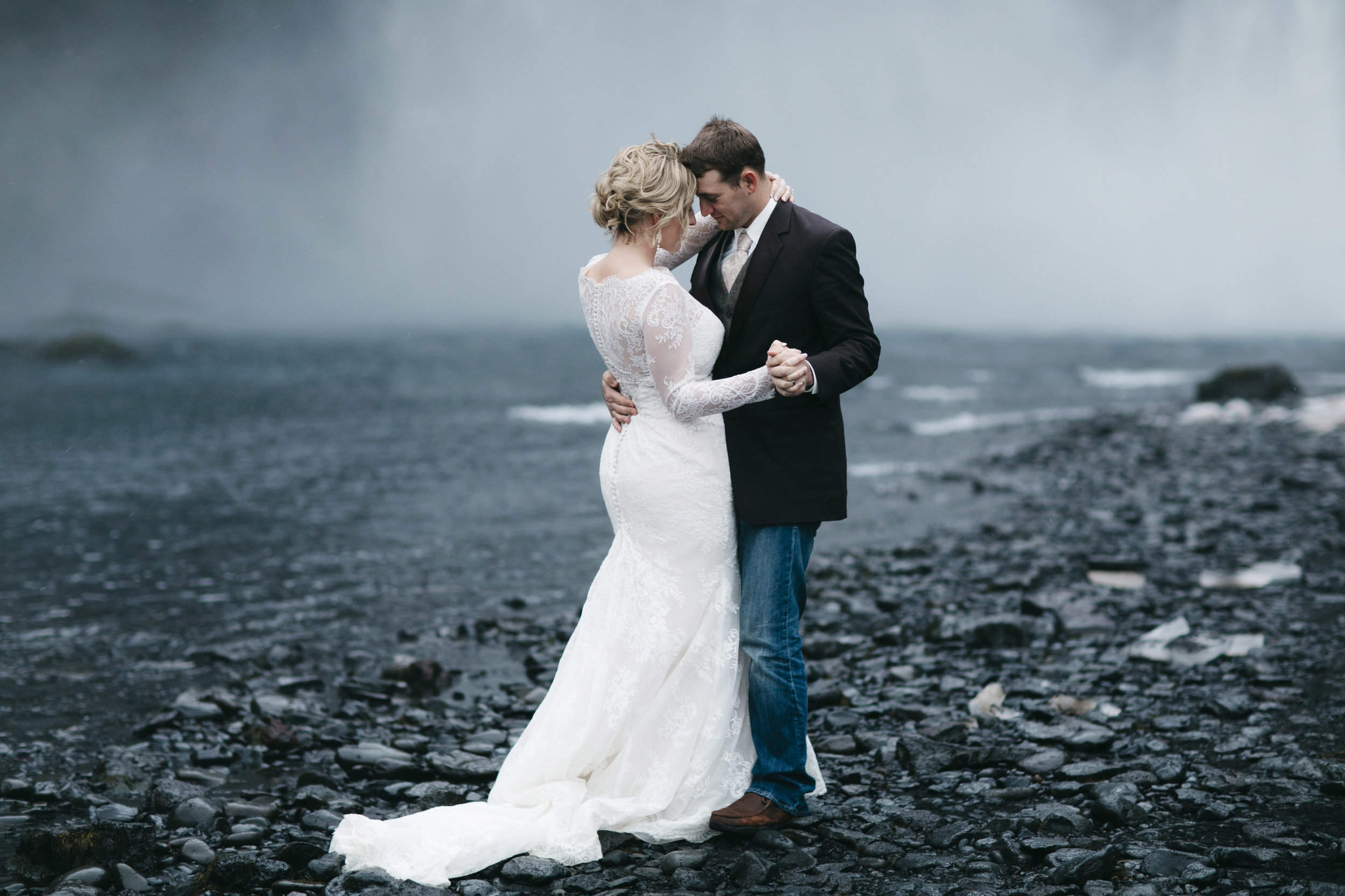 Following their elopement at Skogafoss, a couple shares their first dance by a waterfall with Iceland Elopement photographers Colby and Jess, colbyandjess.com