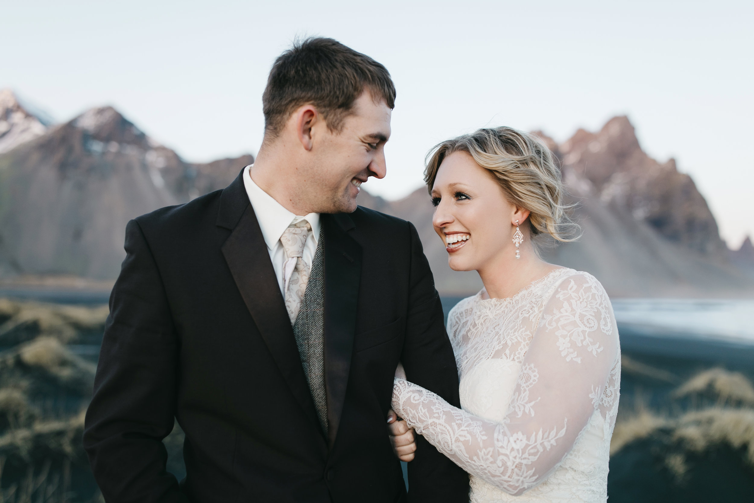 Bride and groom laugh together after their Iceland Elopement with adventure wedding photographers Colby and Jess.