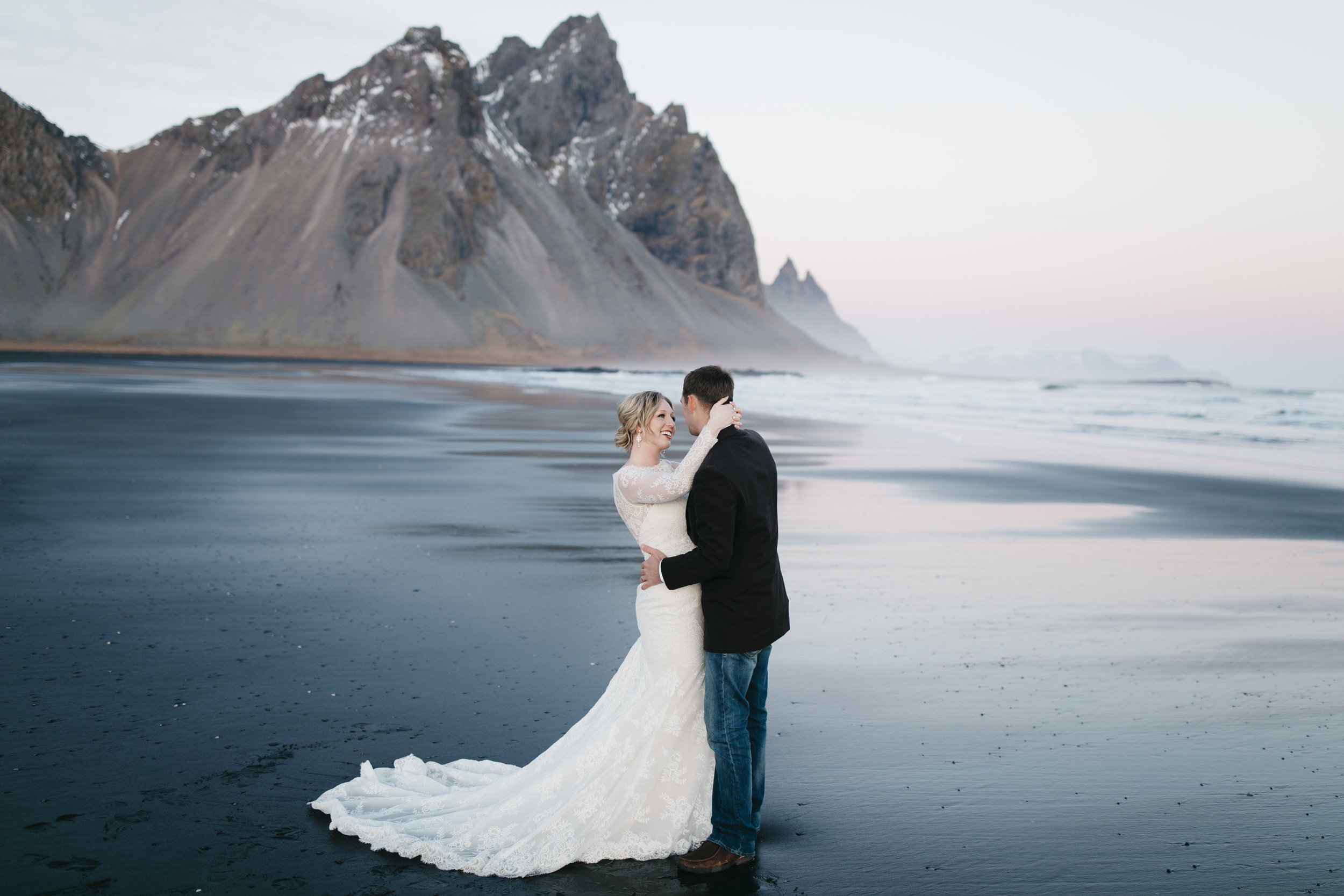 A bride and groom dance on the black sand beaches of Iceland during their adventure elopement photography session by colby and jess.