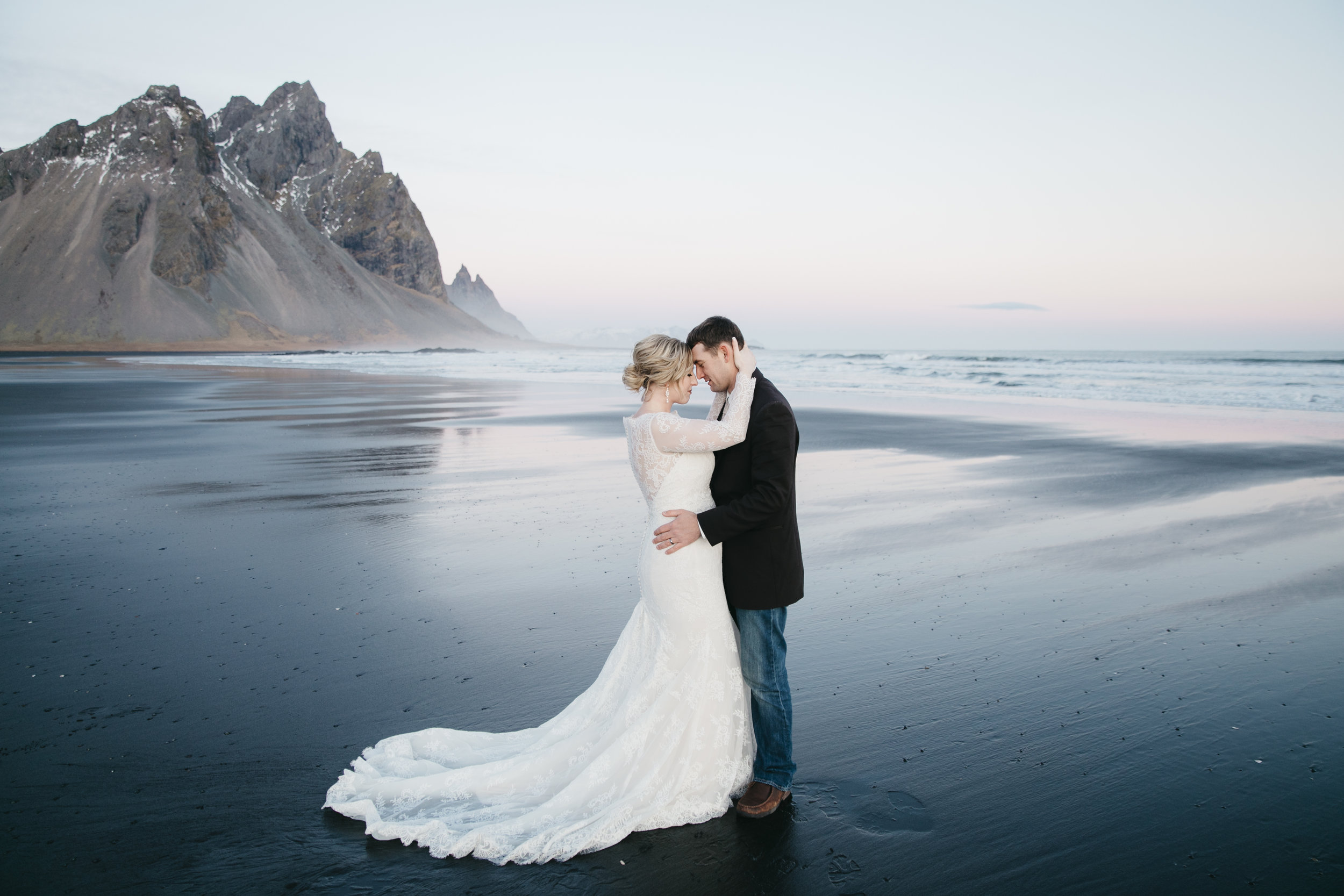 A couple embraces during elopement on the black sand beach in Vestrahorn with Iceland wedding photographers Colby and Jess.