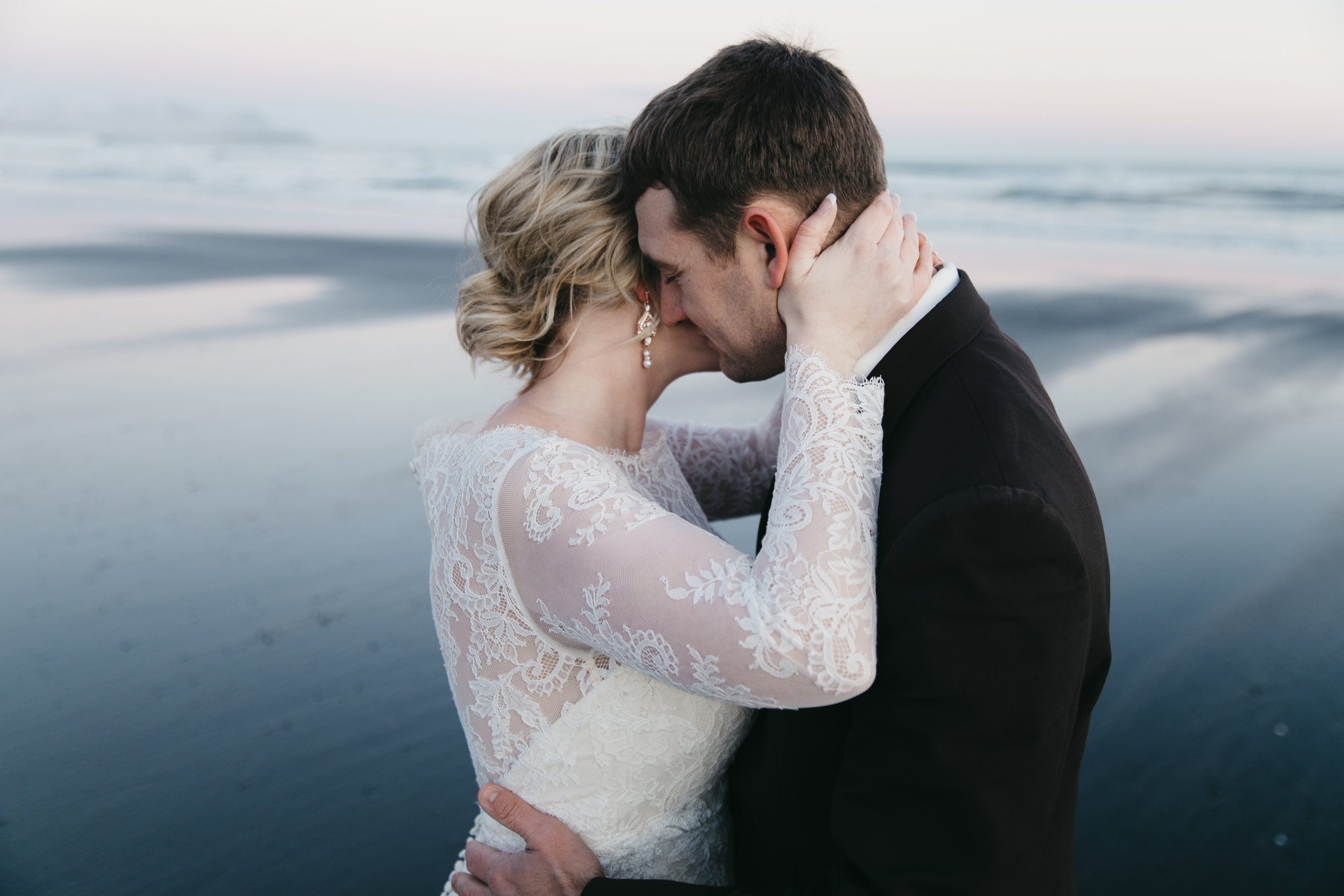 A couple snuggles on the black sand beach during iceland elopement ceremony with destination wedding photographers colby and jess.