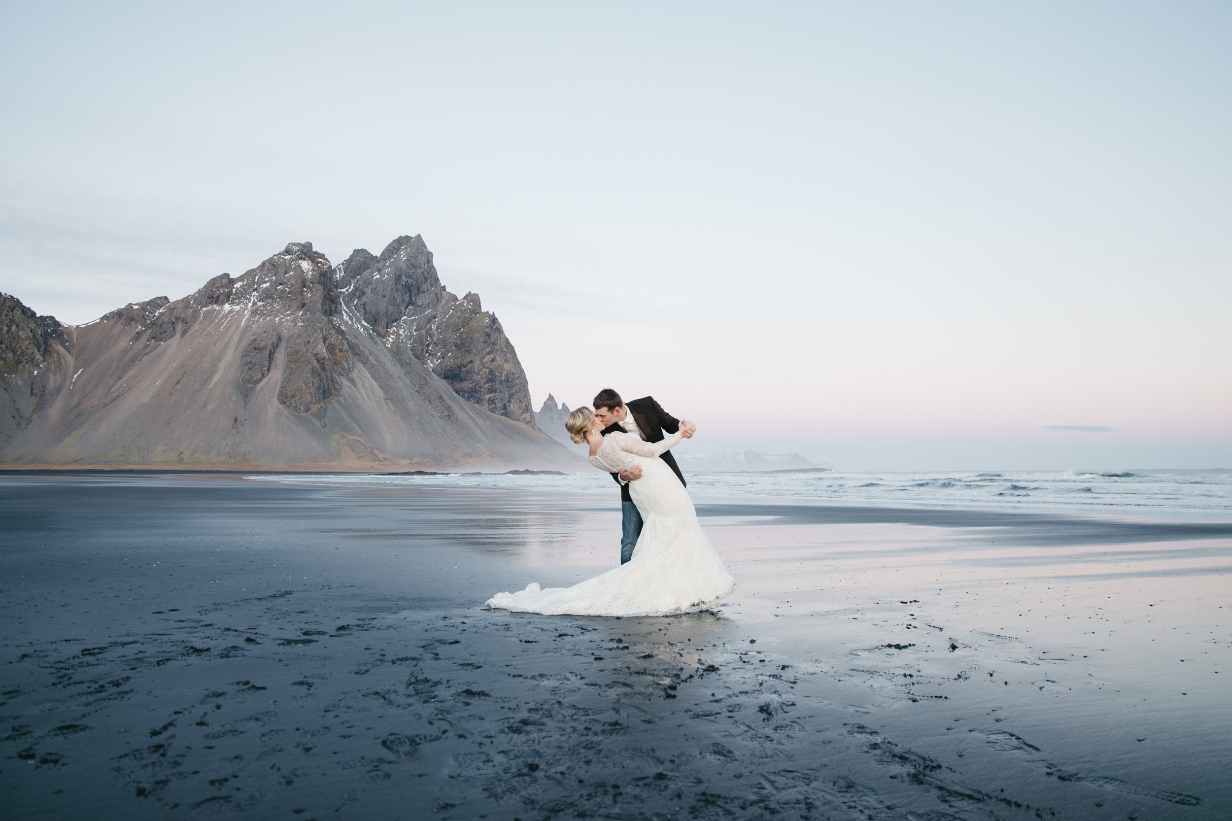 A bride and groom kiss during their Iceland Elopement Photography session in Vestrahorn with Iceland Destination Wedding photographers colby and jess.