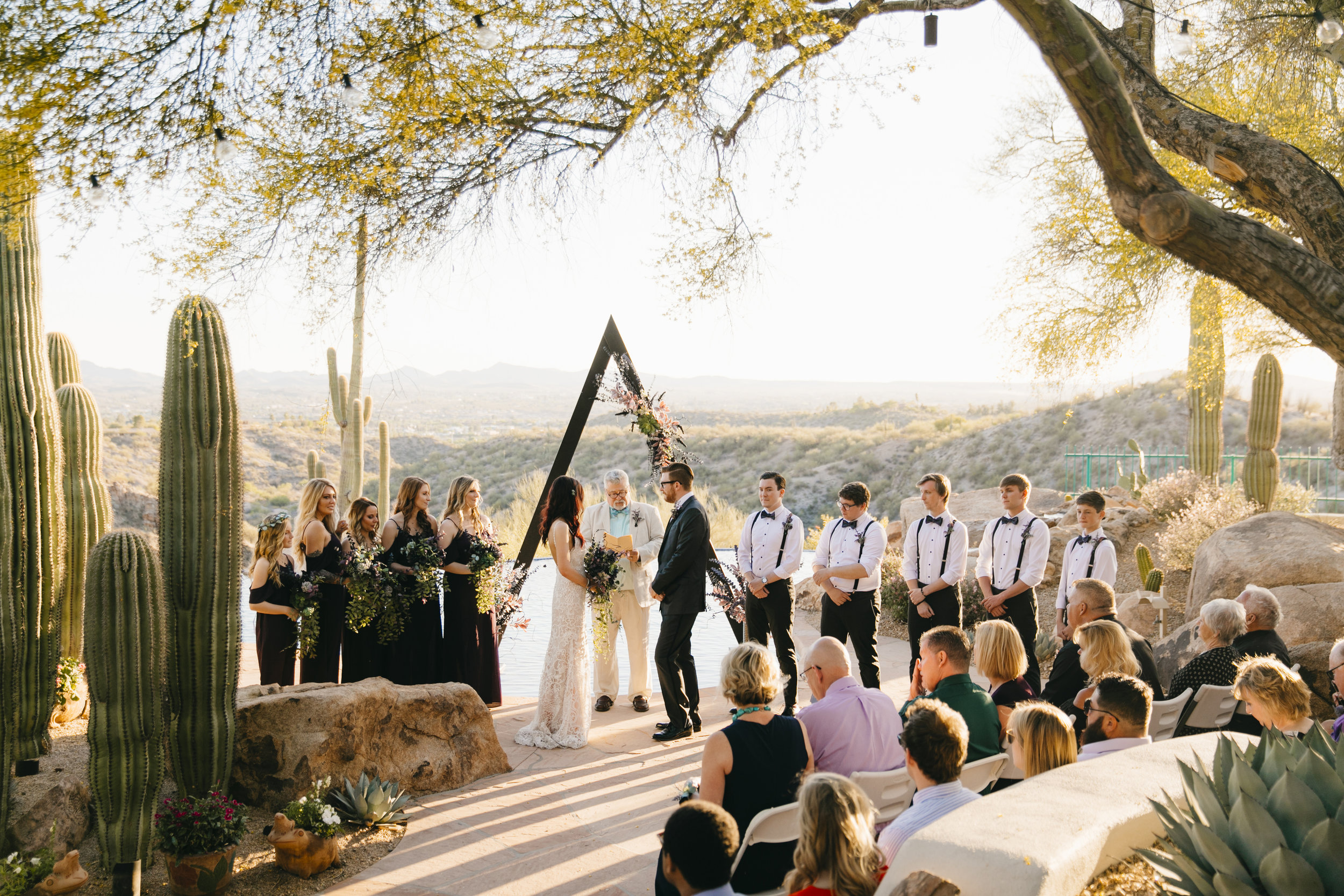 An intimate desert wedding ceremony takes place at sunset by Sedona Destination Elopement Photographers Colby and Jess.
