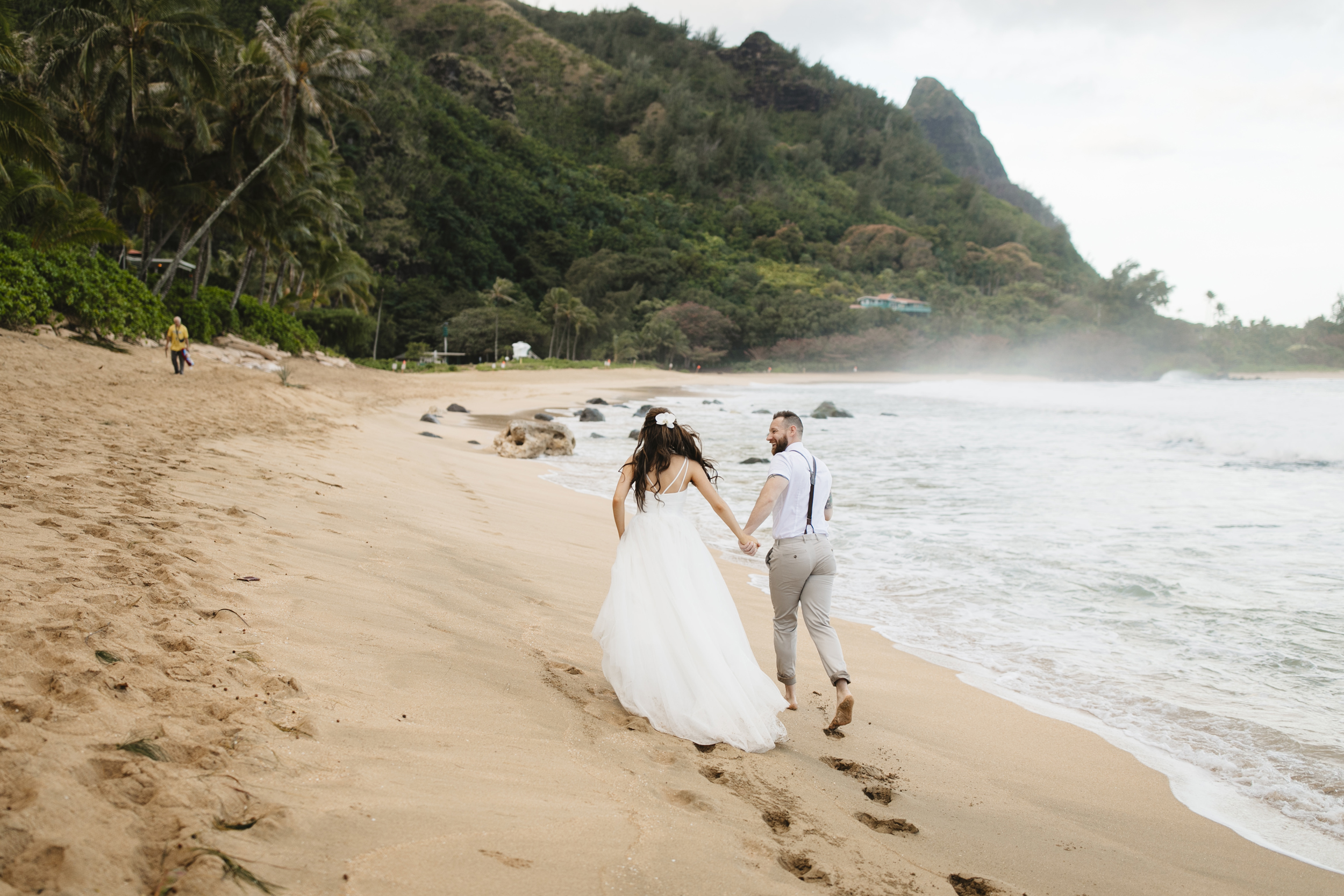An adventurous couple runs down Tunnels Beach after their Kauai Elopement with Hawaii Destination Wedding Photographers Colby and Jess