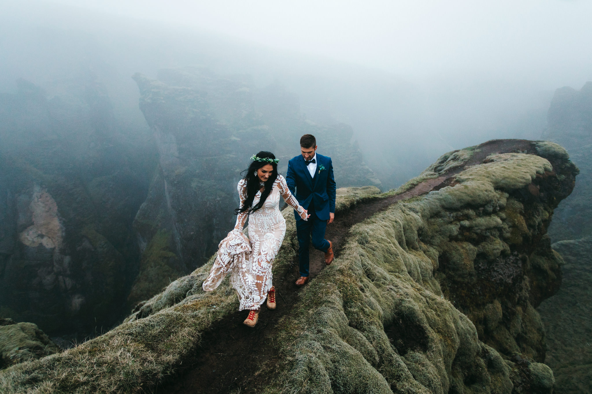An adventurous bride and groom walk above a canyon with their Iceland Destination Elopement Photographers Colby and Jess