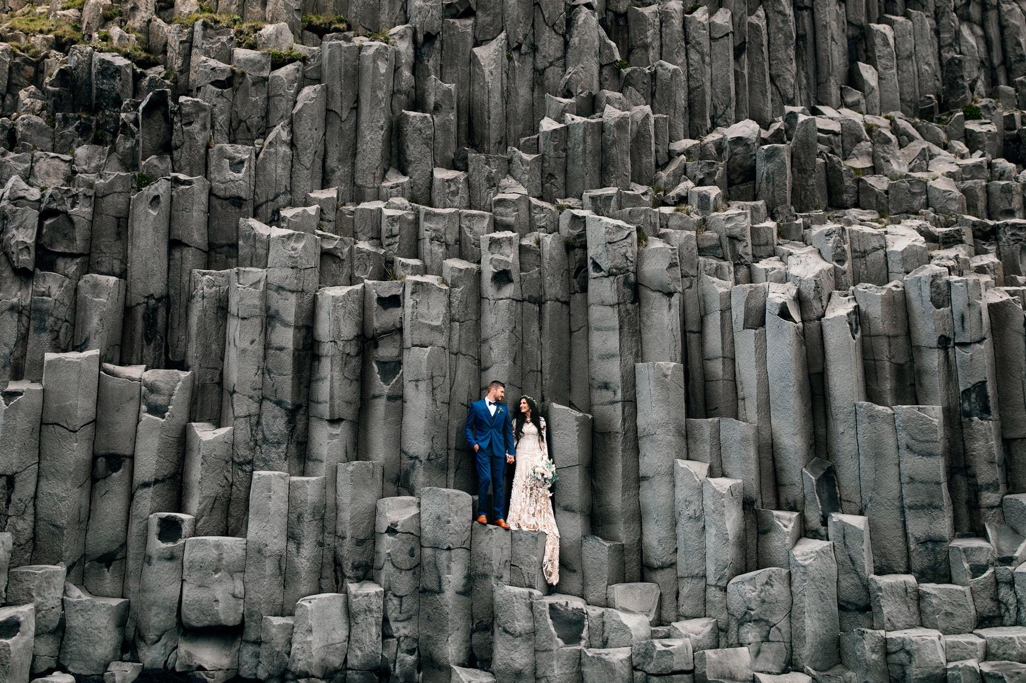 A couple stands on Basalt Columns at the Black sand beach with Iceland Destination Elopement Photographers Colby and Jess