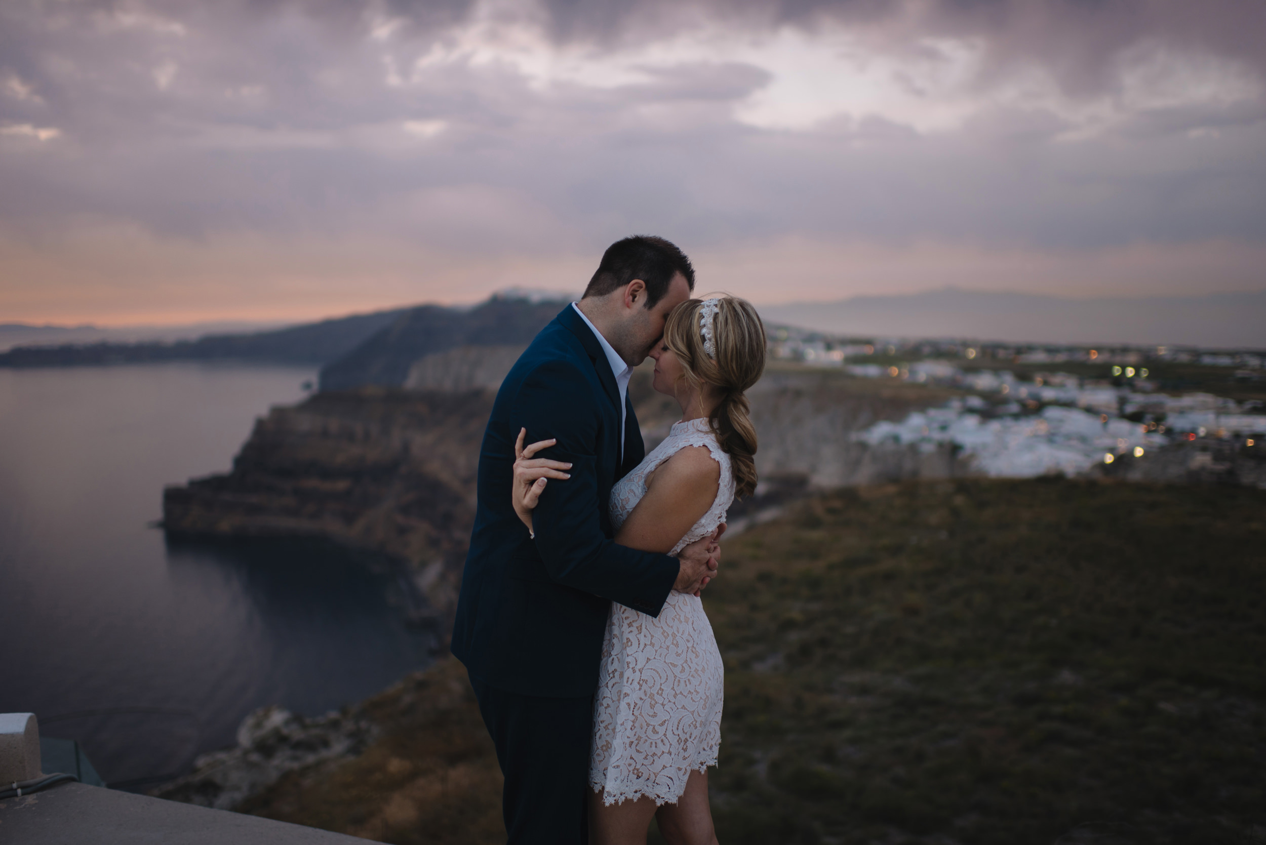 The sunsets over Santorini as a couple kisses during their Destination Elopement with Greece Wedding Photographers Colby and Jess