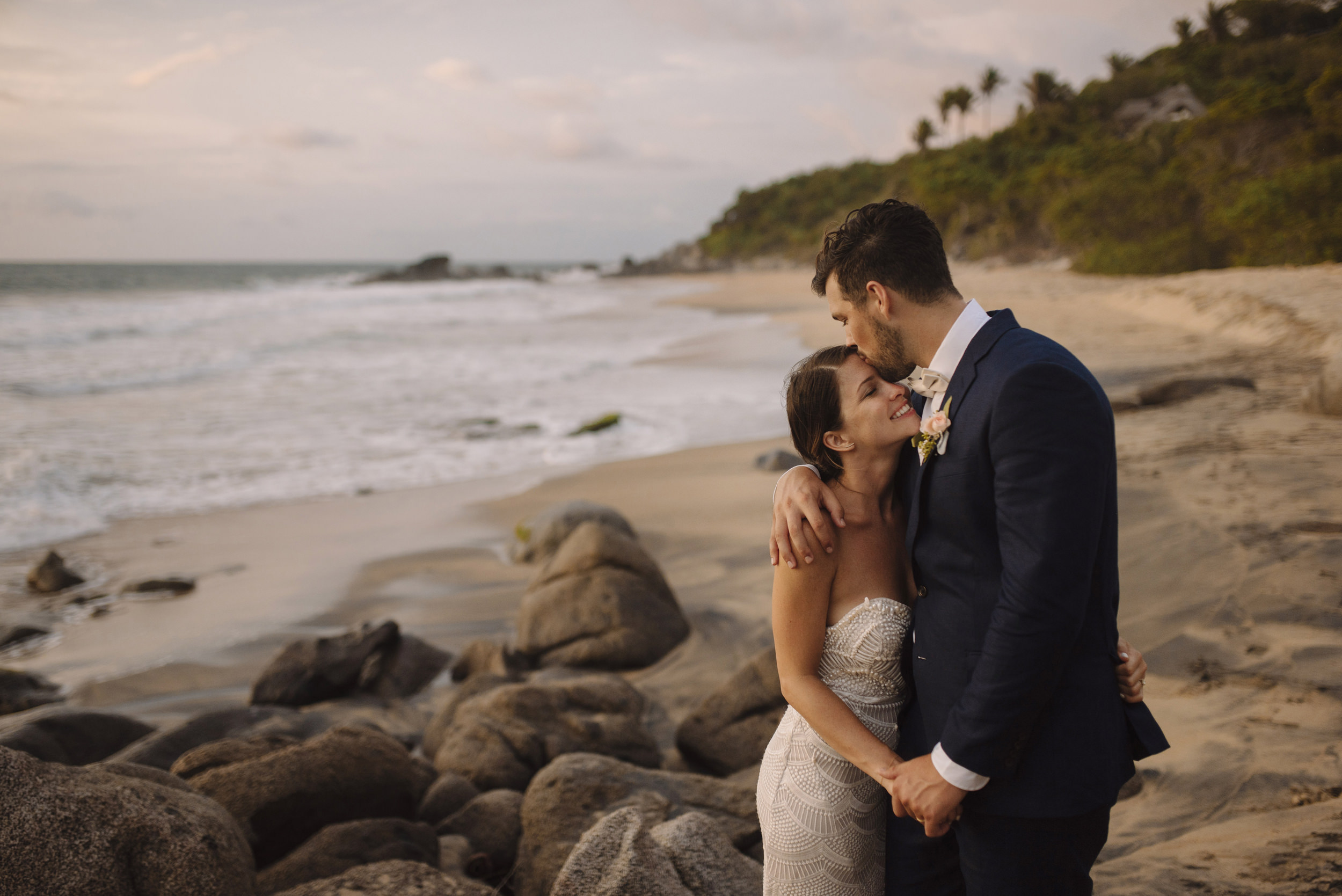 A groom lovingly kisses his bride on the forehead during their Sayulita Wedding with Puerto Vallarta Destination Elopement photographers Colby and Jess