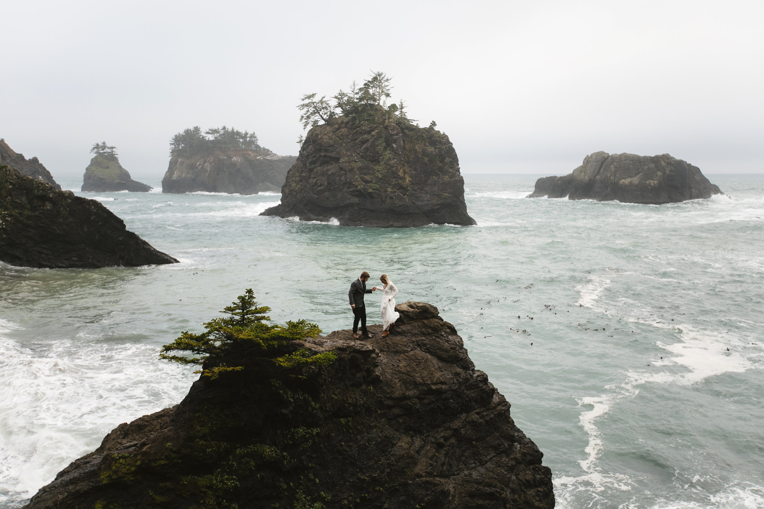 A groom helps his bride climb along the Oregon Coast during their adventure vow renewal with Cannon Beach Destination Elopement Photographers Colby and Jess