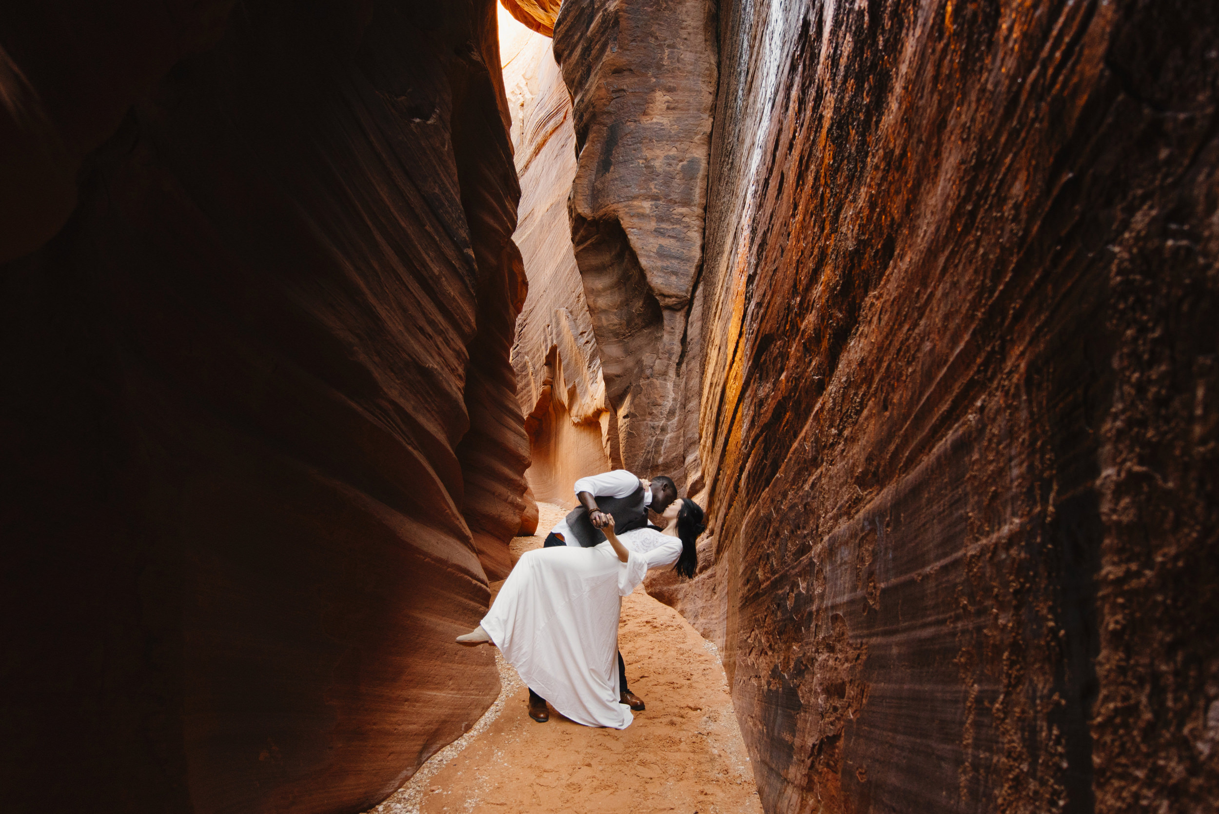 A man dips his wife and kisses her while dancing in a slot canyon during their Antelope Canyon couples adventure photography session with Utah Destination Elopement Photographer Colby and Jess