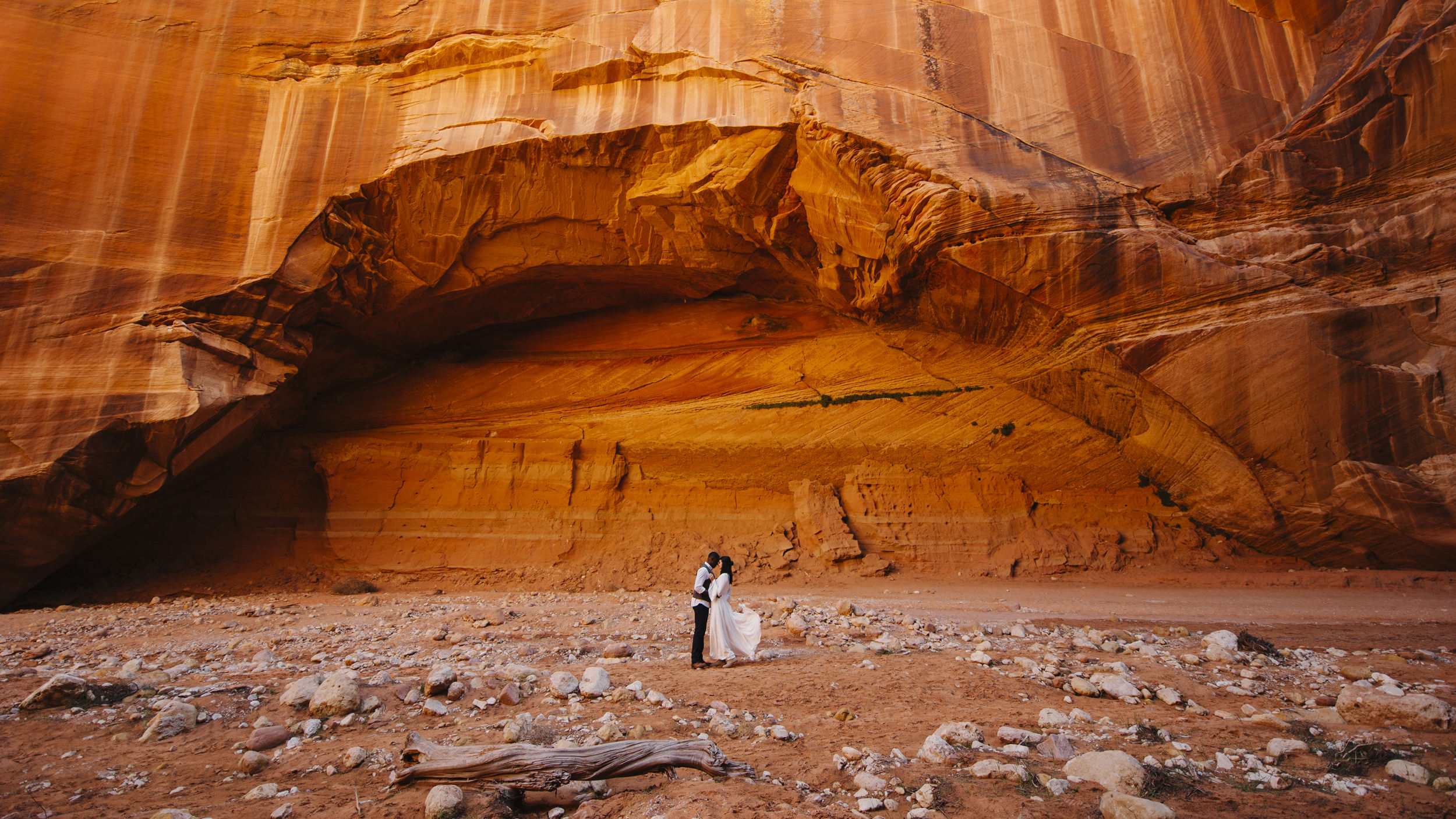 A couple stands under an archway at Antelope Canyon with Utah Destination Elopement Photographer Colby and Jess