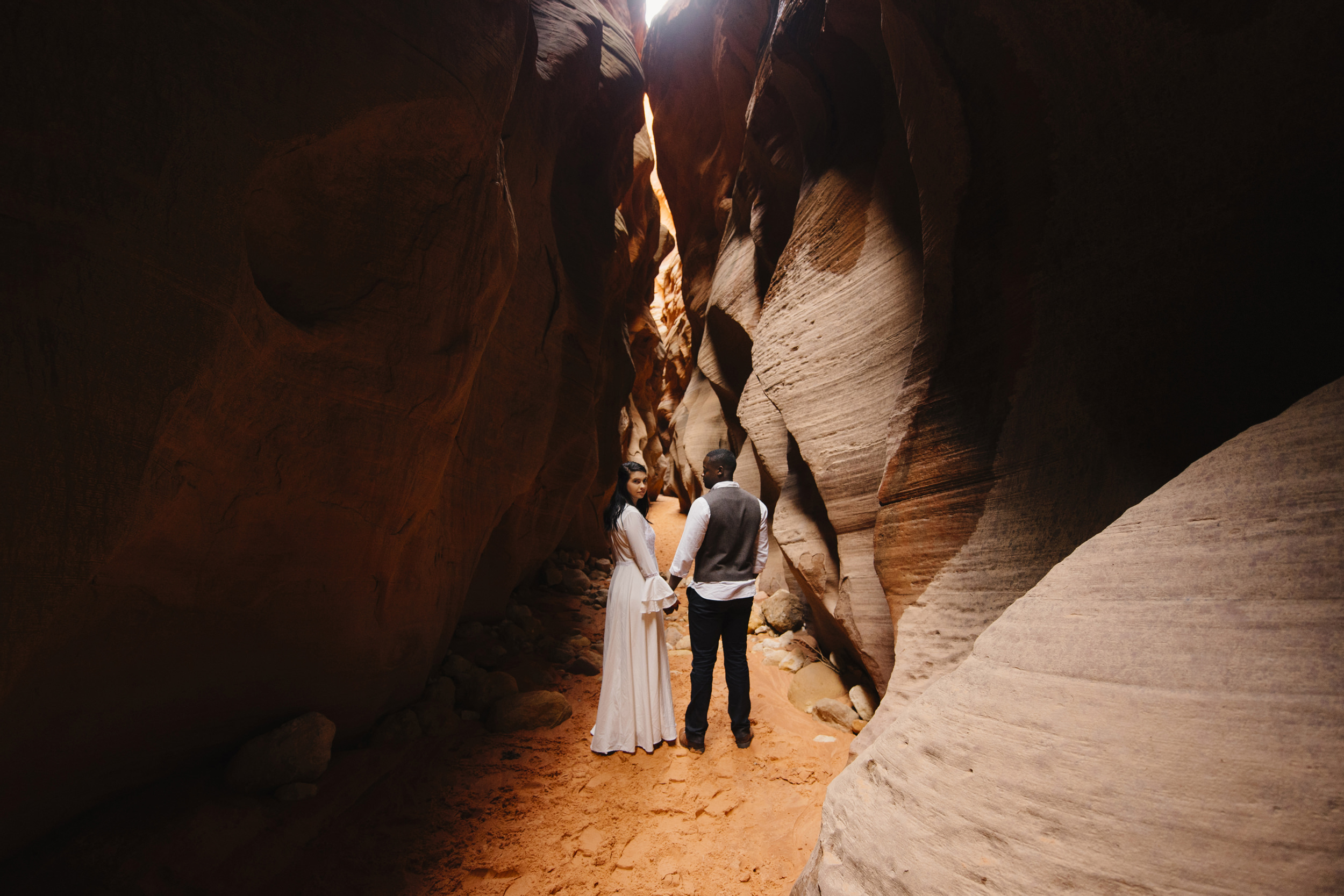 A couple explores Antelope Canyon during their adventure photography session by Utah Destination Elopement Photographer Colby and Jess