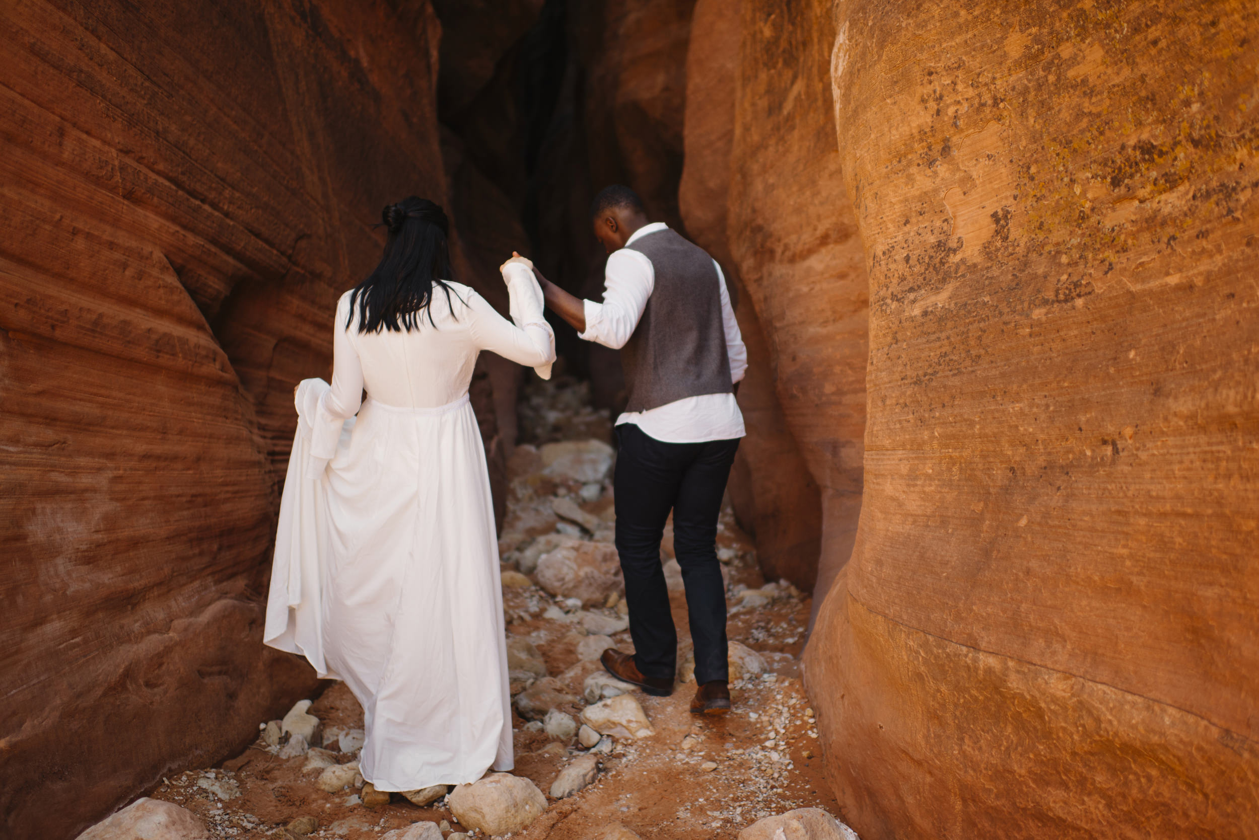 A man holds his wife's hand leading her into a slot canyon during their Antelope Canyon Couple's Adventure Photography Session with Utah Destination Elopement Photographer Colby and Jess