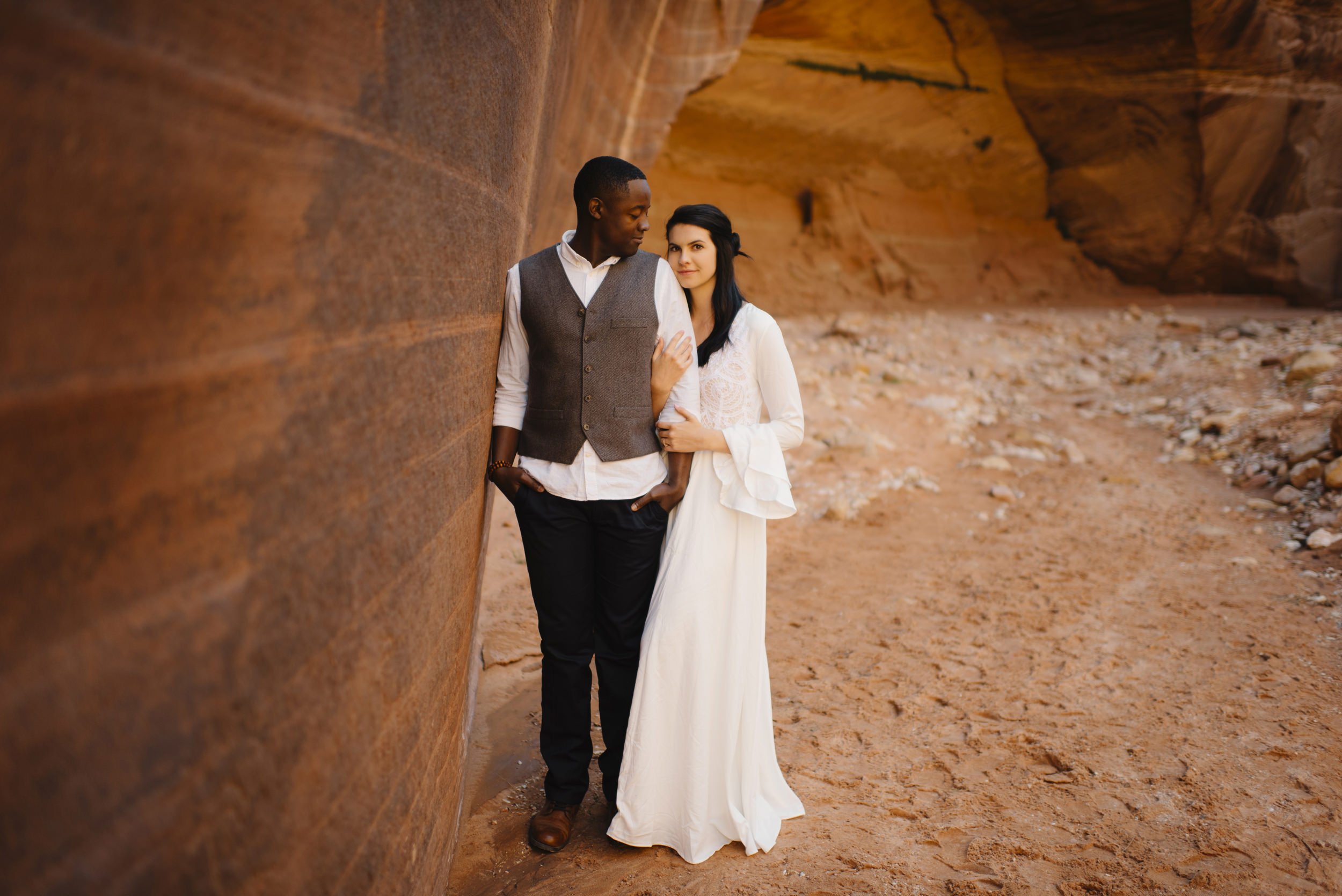 A woman holds her husbands arm during their Slot Canyon Couples Adventure Photography Session with Utah Destination Elopement Photographer Colby and Jess