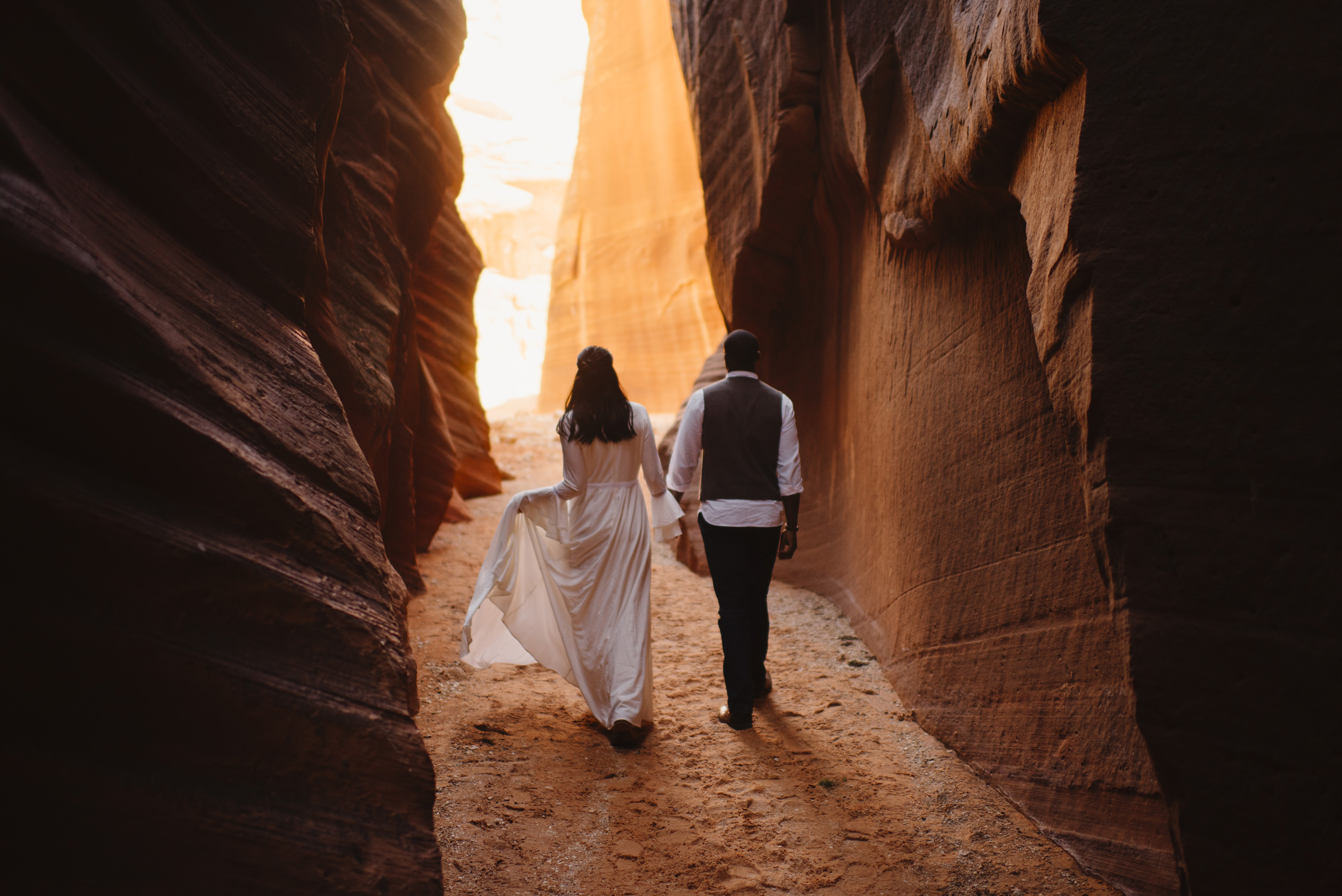 A couple is holding hands while exploring a slot canyon during their adventure engagement photography session with Utah Destination Elopement Photographer Colby and Jess