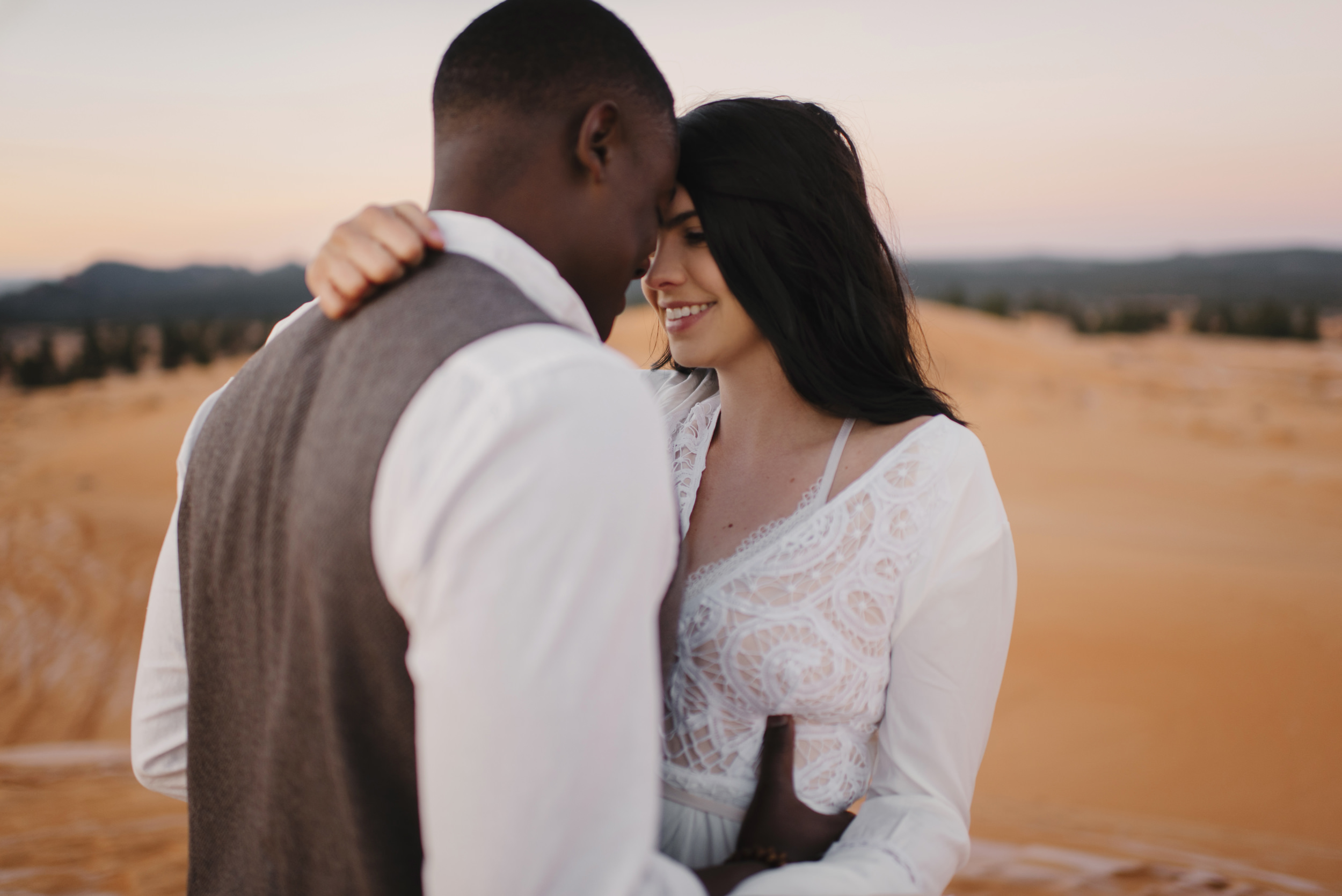 A couple snuggles at Coral Pink Sand Dunes during their adventure engagement photography session with Utah Destination Elopement Photographer Colby and Jess