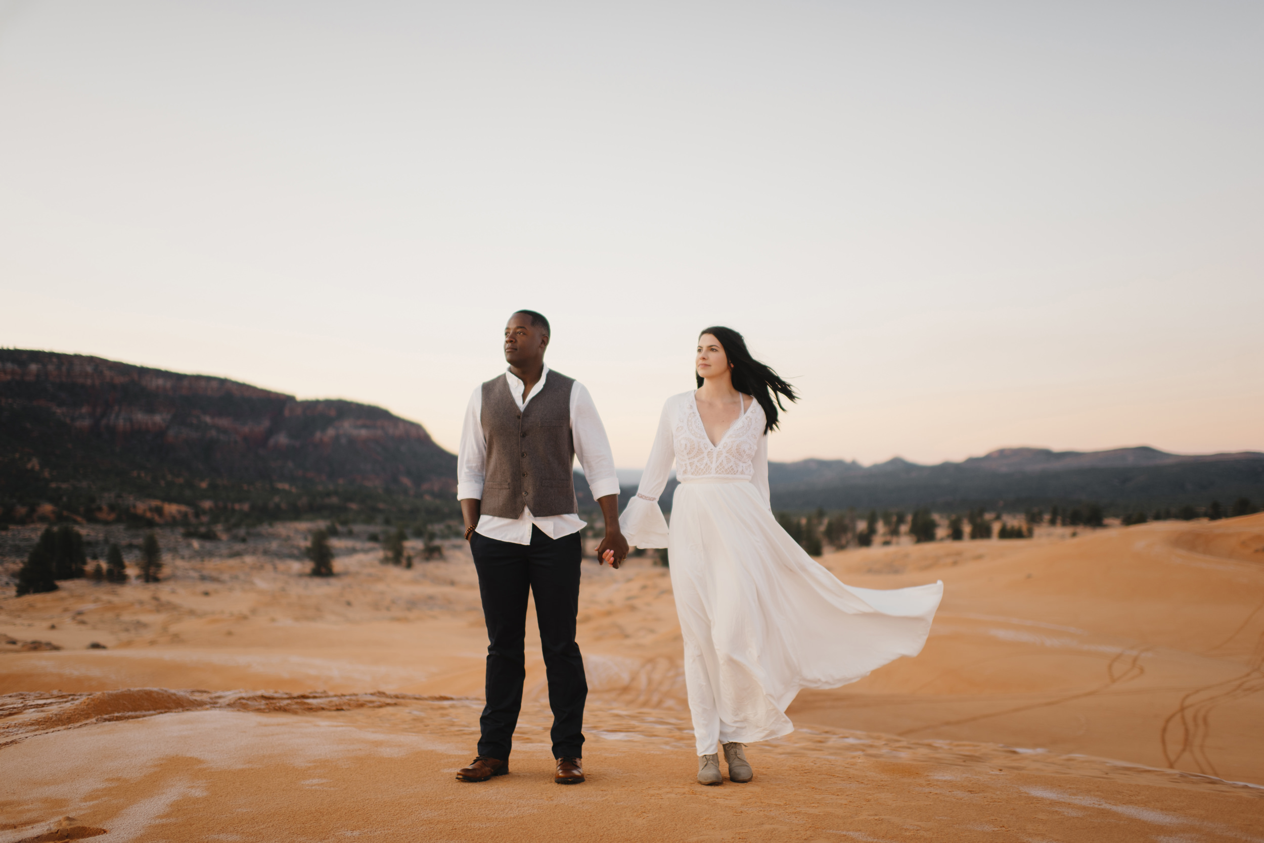 A couple holds hands while exploring coral pink sand dunes with Utah Destination Elopement Photographer Colby and Jess