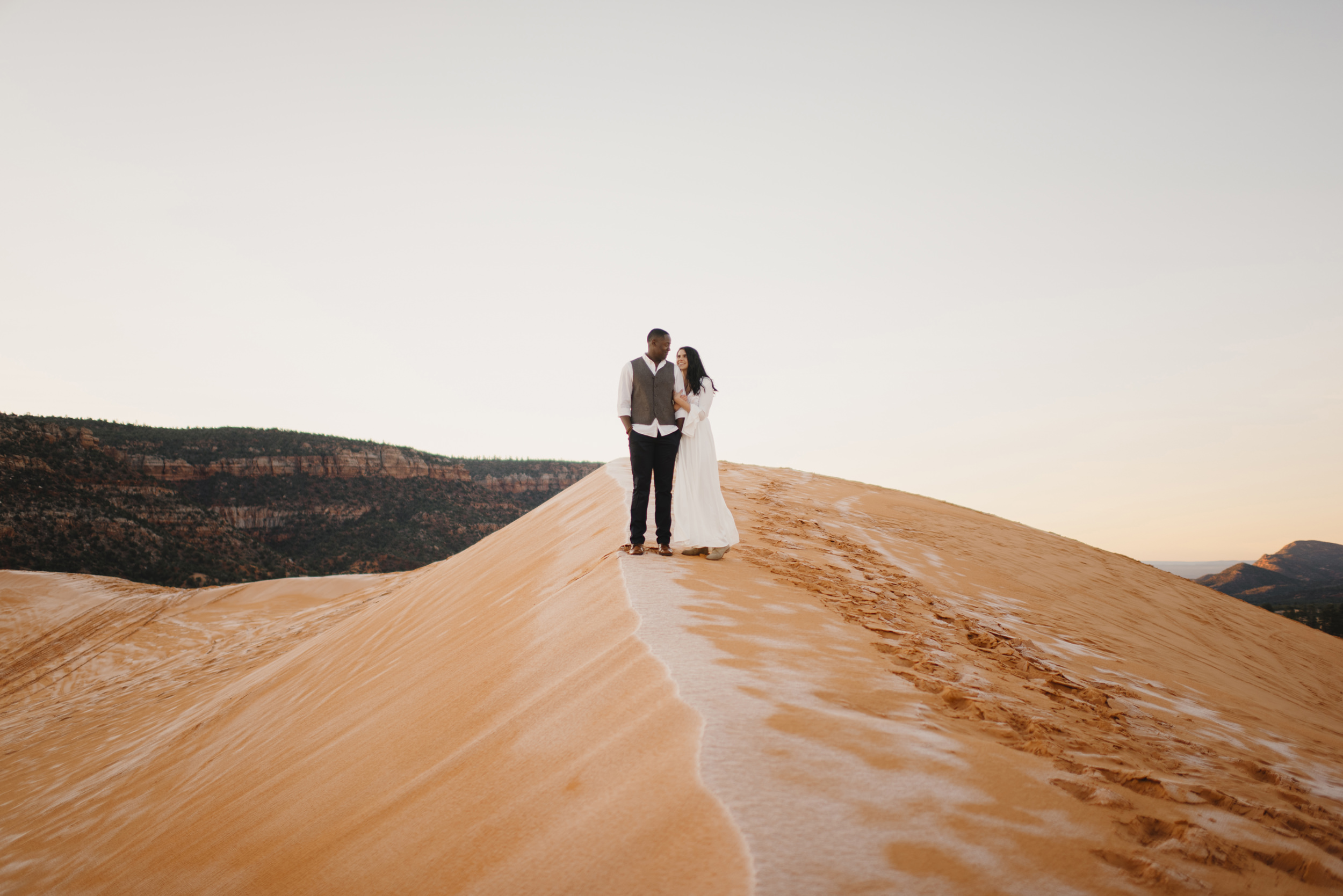 A couple stands side by side during their Coral Pink Sand Dunes adventure engagement photography session by Utah Destination Elopement Photographer Colby and Jess