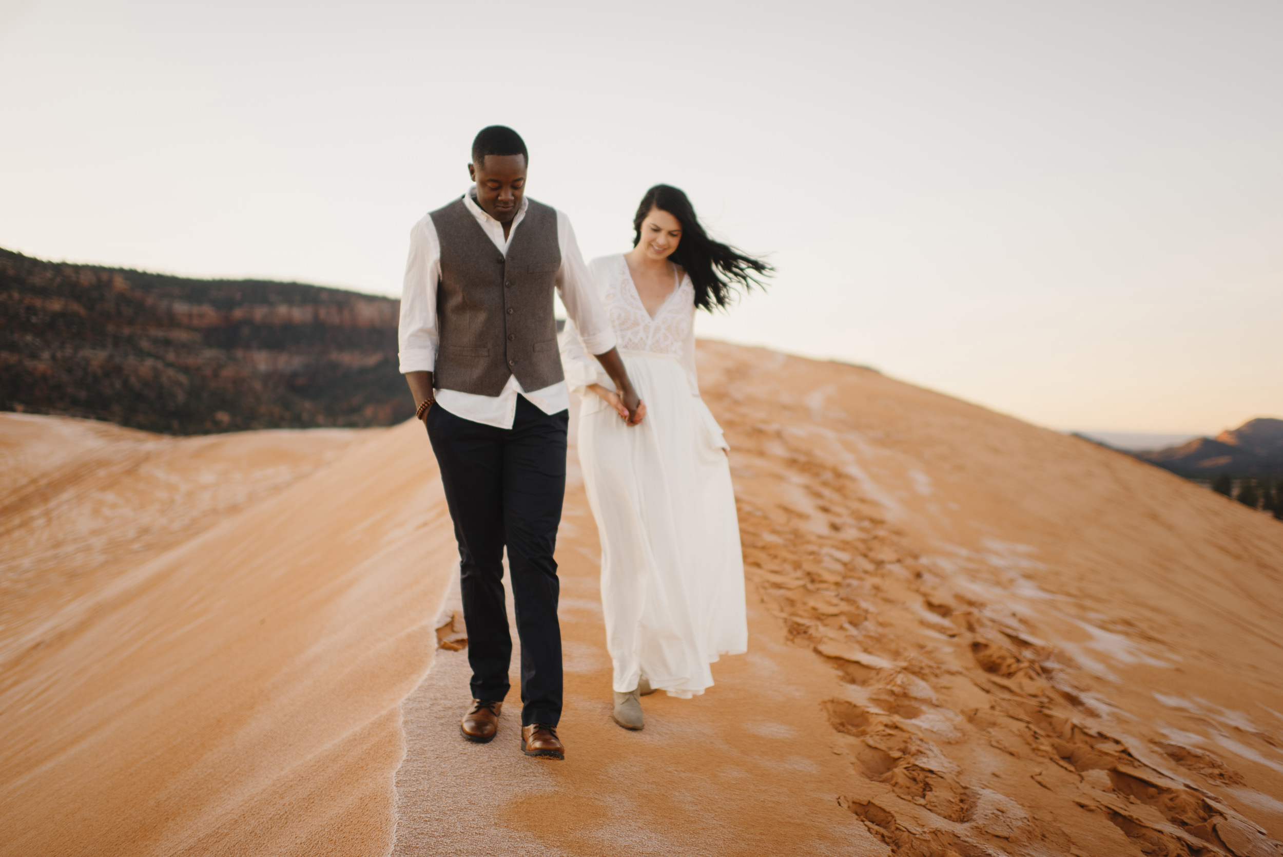 Holding hands a couple smiles during their Coral Pink Sand Dunes Engagement Photography Session by Utah Destination Elopement Photographer Colby and Jess