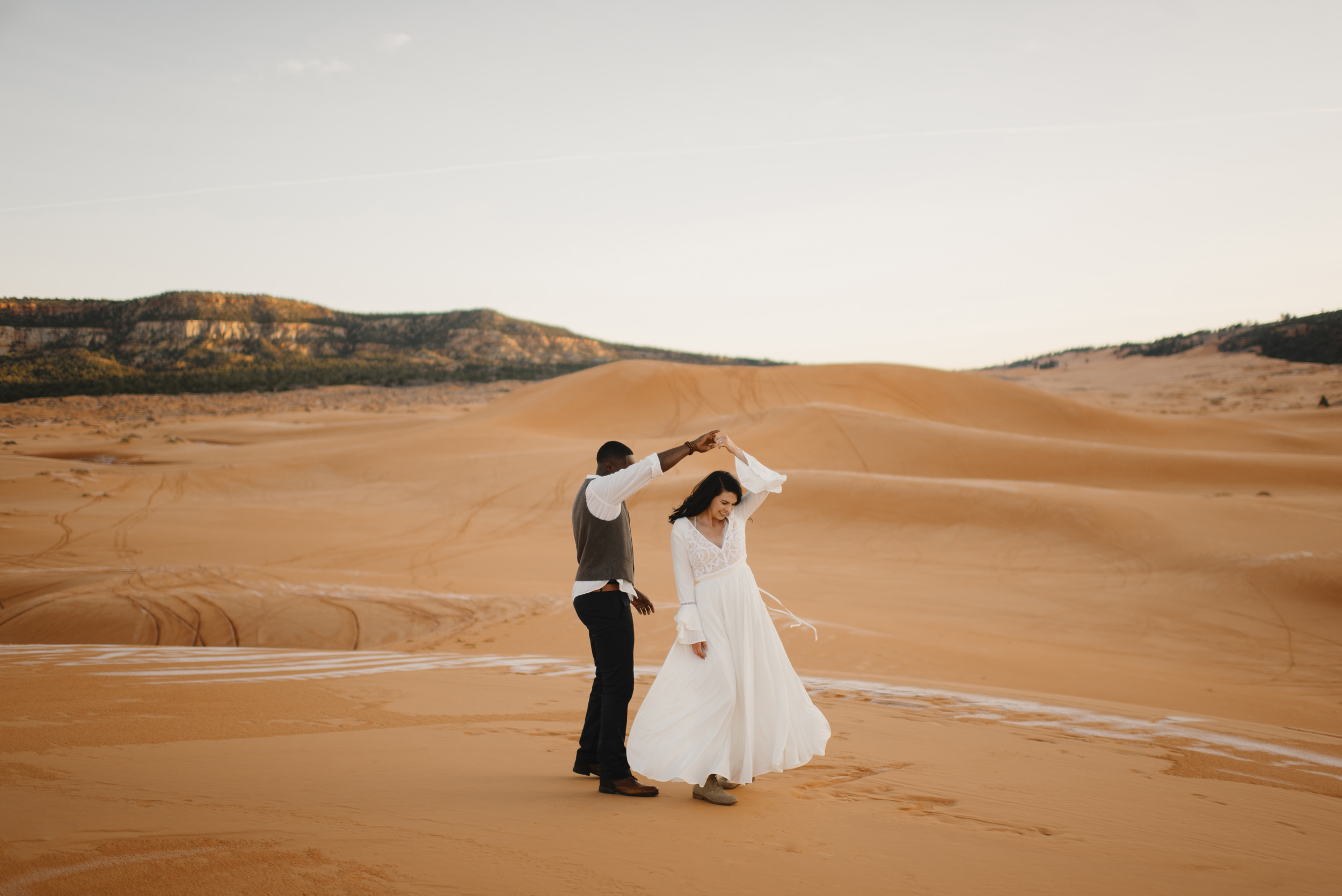 A couple dances in Coral Pink Sand Dunes during their adventure engagement photography session by Utah Destination Elopement Photographer Colby and Jess