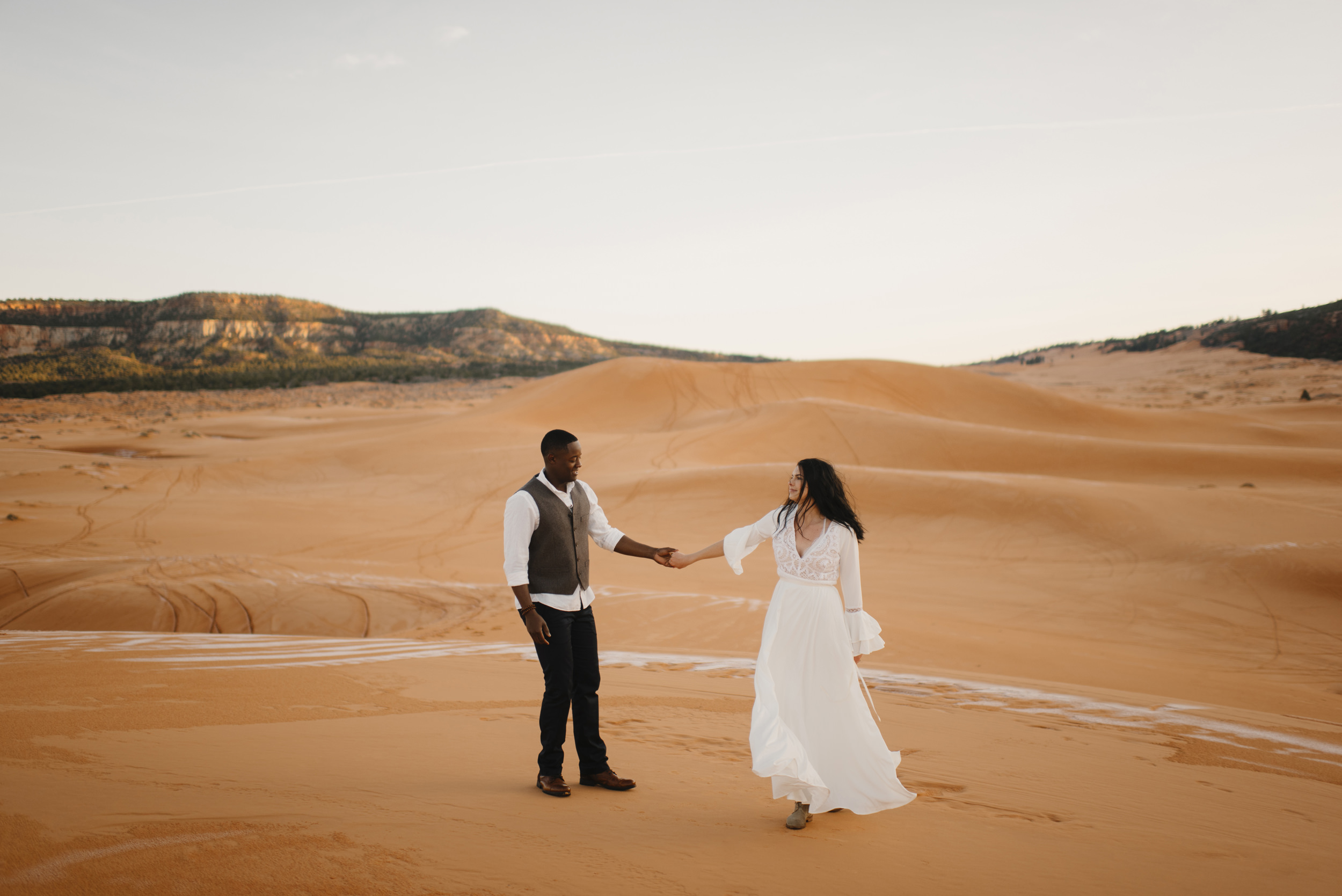 A man and woman dance during their Coral Pink Sand Dunes Adventure Couples Photography Session by Utah Destination Elopement Photographer Colby and Jess