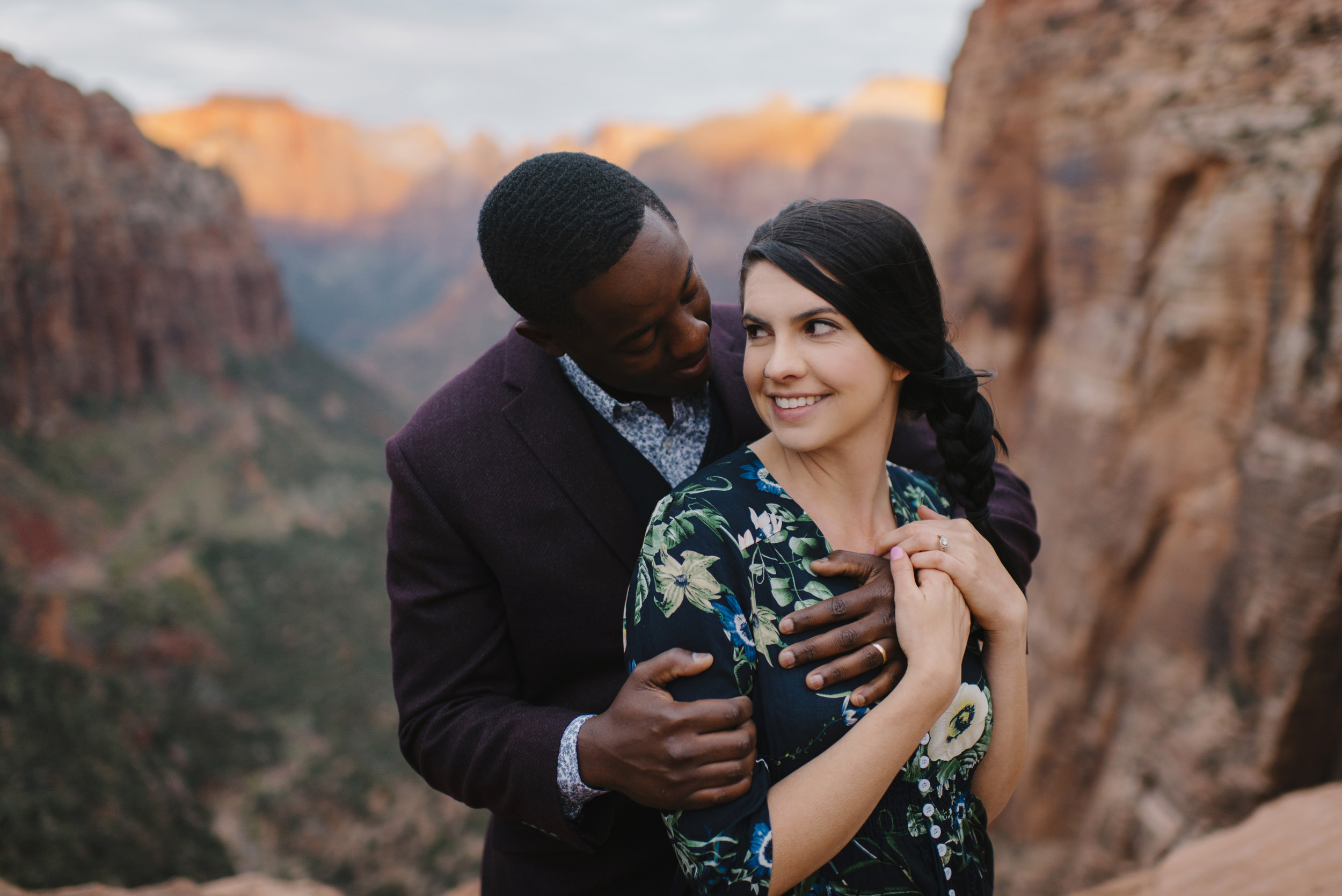 A woman is held by her husband during their Angels Landing Engagement Photography Session with Zion National Park Adventure Elopement Photographer Colby and Jess
