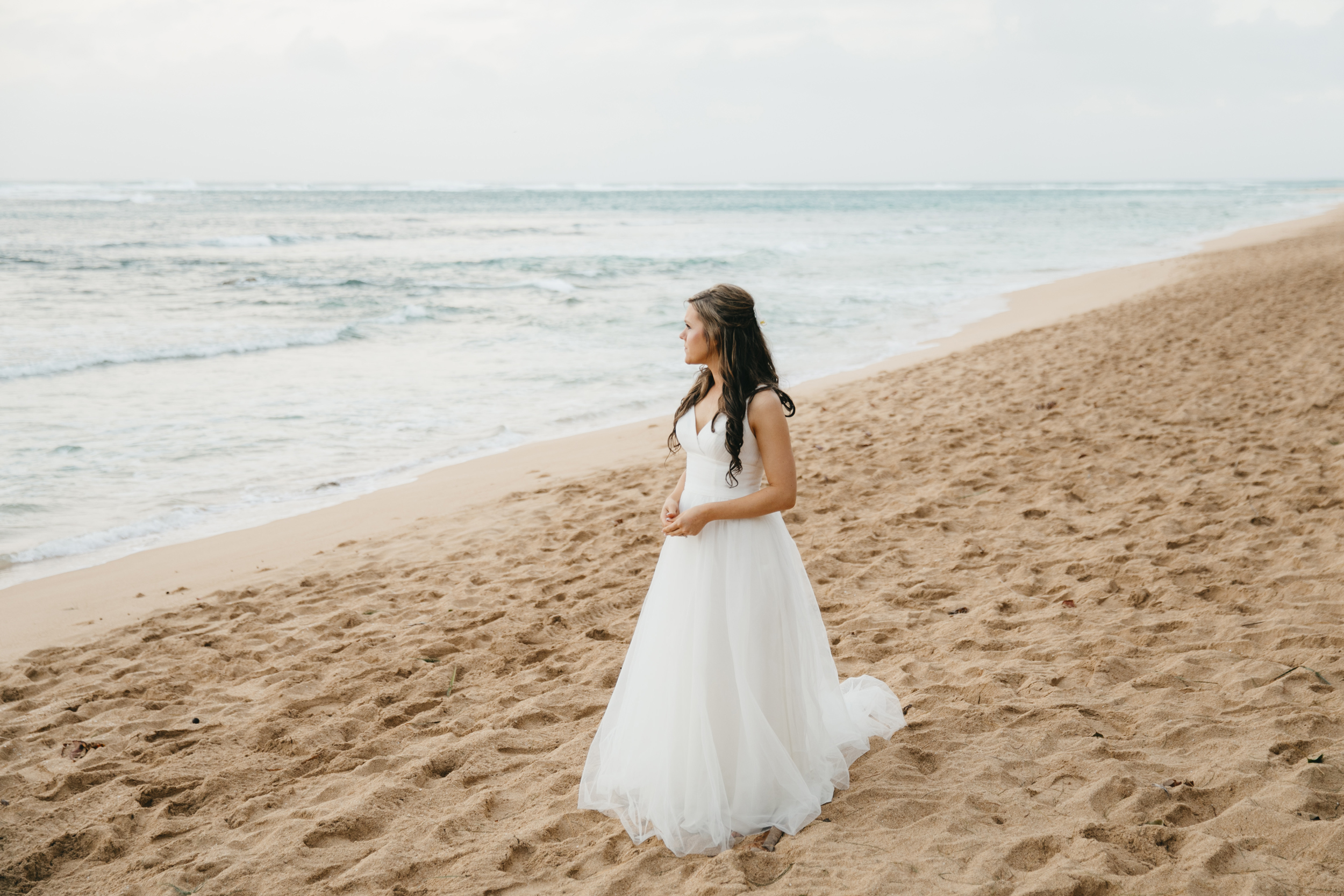 Bride stands on Tunnels Beach during Kauai Elopement by Adventure Wedding photographers Colby and Jess