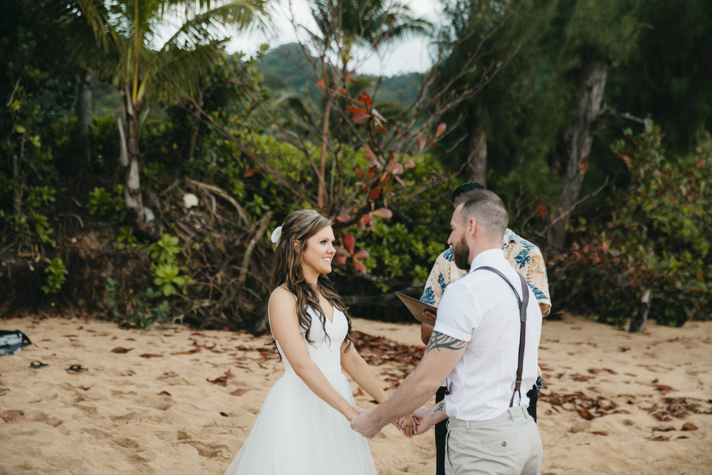 Vows are exchanged during Tunnels Beach wedding ceremony with Kauai Elopement photographers Colby and Jess