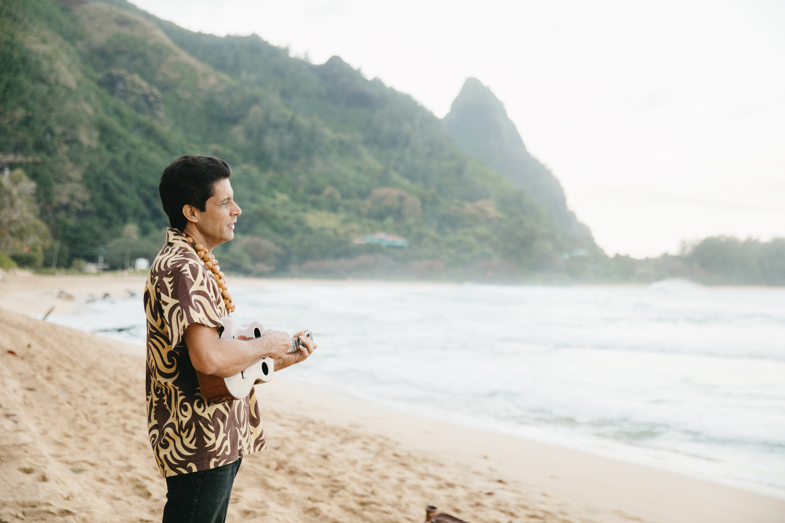 Ukulele player during Tunnels Beach Wedding Ceremony with Kauai Elopement Photographers Colby and Jess