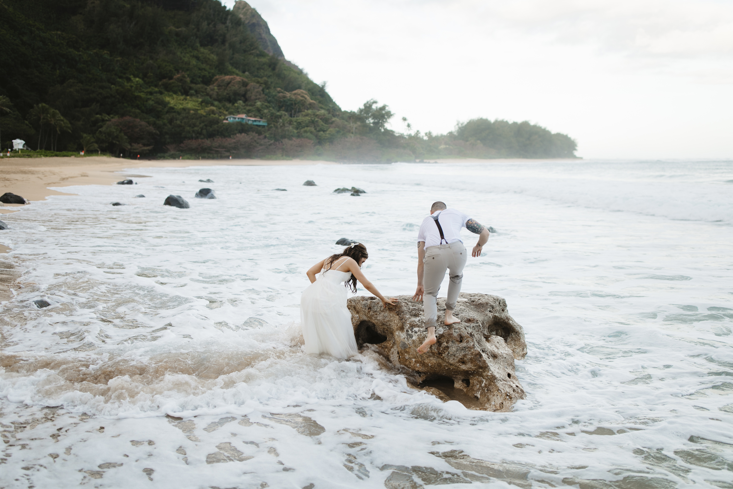 A couple playing on the beach after Tunnels Beach Elopement Ceremony by Kauai Wedding Photographers Colby and Jess