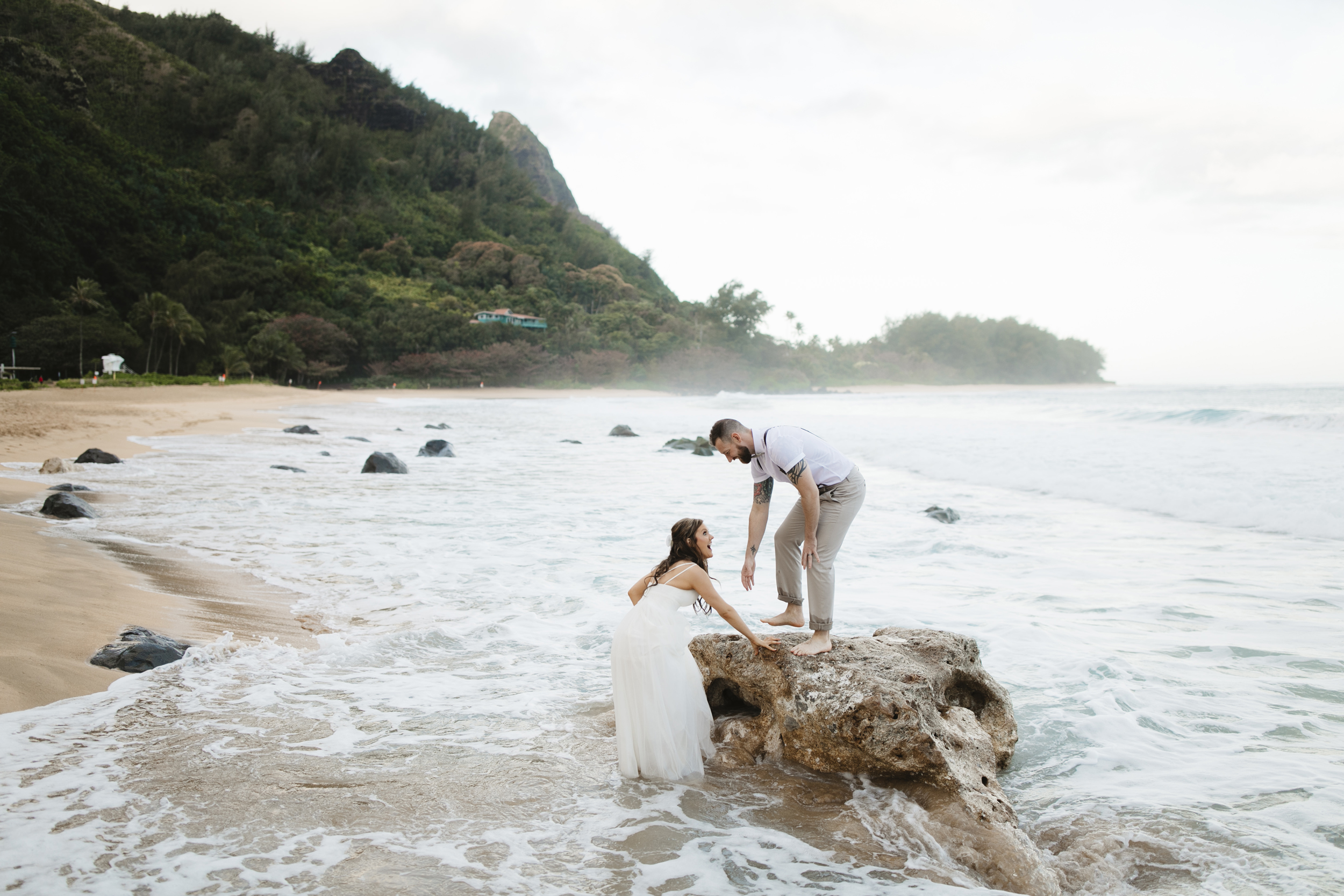 A bride and groom playing on the beach after Tunnels Beach Elopement Ceremony by Kauai Wedding Photographers Colby and Jess