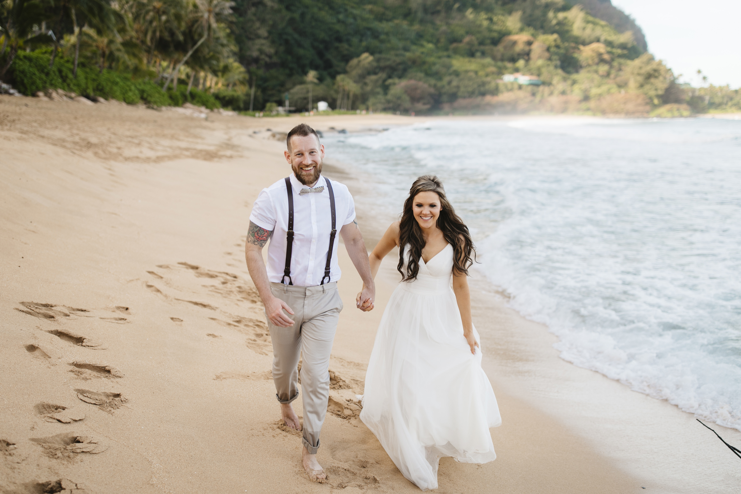 A couple runs on the beach after Tunnels Beach Elopement Ceremony by Kauai Wedding Photographers Colby and Jess