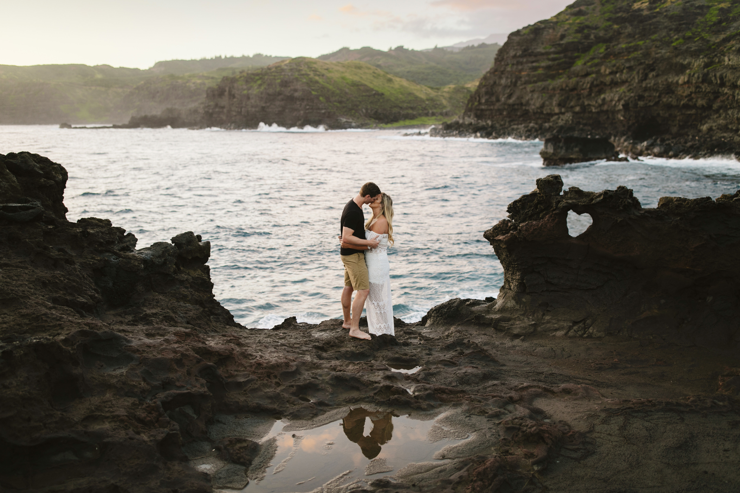 A couple kisses in Maui during their adventure engagement session by Hawaii Elopement Photographers Colby and Jess