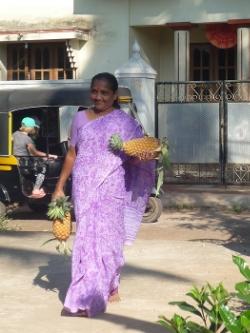 Här kommer Usha med dagens ananas. Varje dag serveras färsk frukt under förmiddagen.