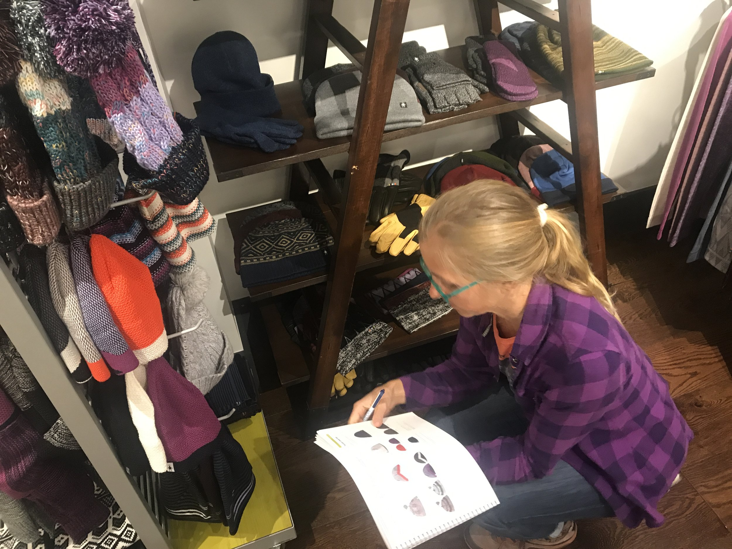 Erin selecting Smartwool accessories for next fall. Come check out our hat and scarf forest at the shop to check out all the cozy accessories to stay warm through the winter.