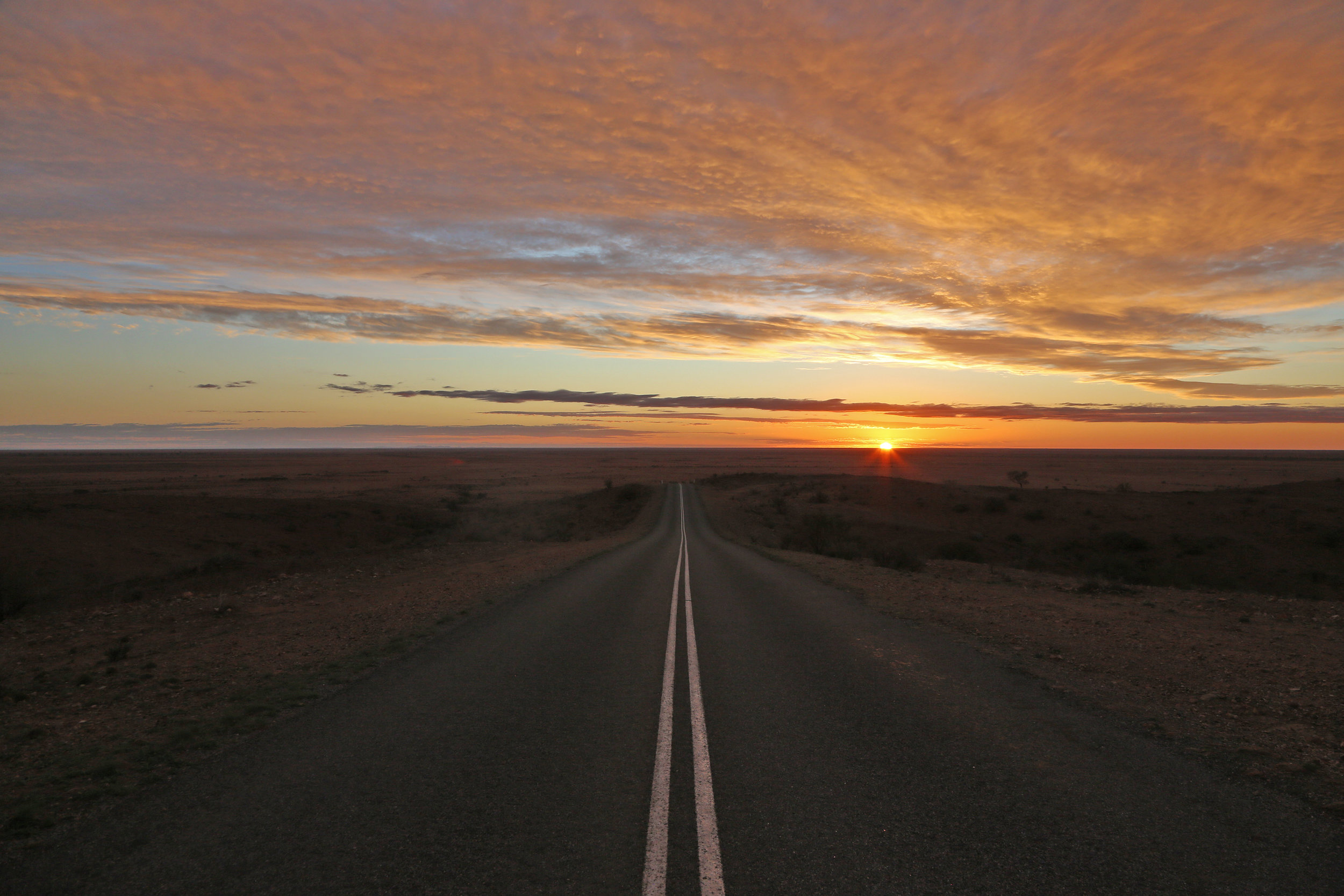 Just a few steps from this road, we get out of the car to watch the sunset over a far-flung horizon.