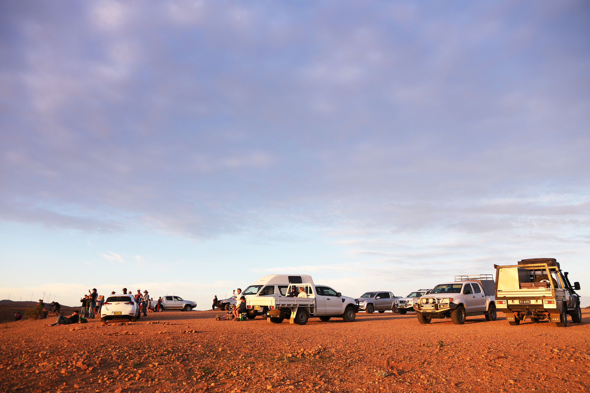 Over a dozen cars full of people (both locals and tourists) gather at the Mundi Mundi lookout to watch the sunset.