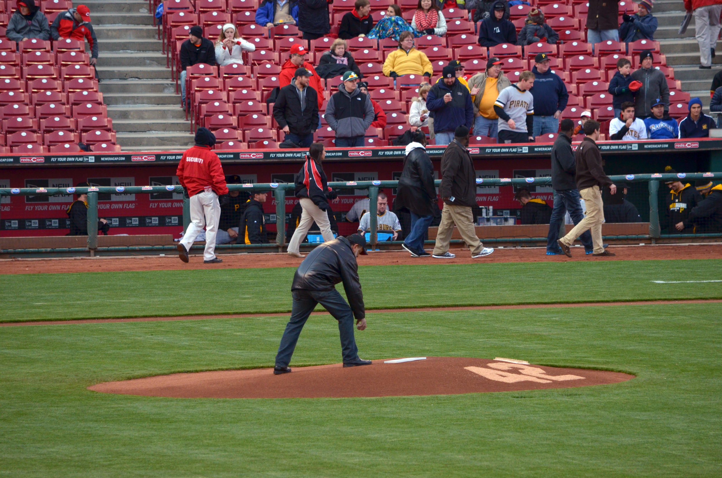 Clay Holland (Owner and President) placing opening game ball on pitcher's mound.