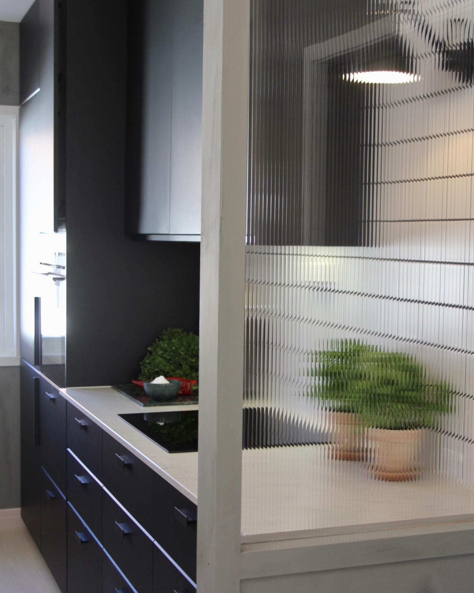Fluted glass can be found in similar properties from the late 50's and were installed to allow light to pass through while separating the kitchen.
