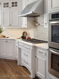 Classic white kitchen design with tile mosaic backsplash and stainless steel hood.